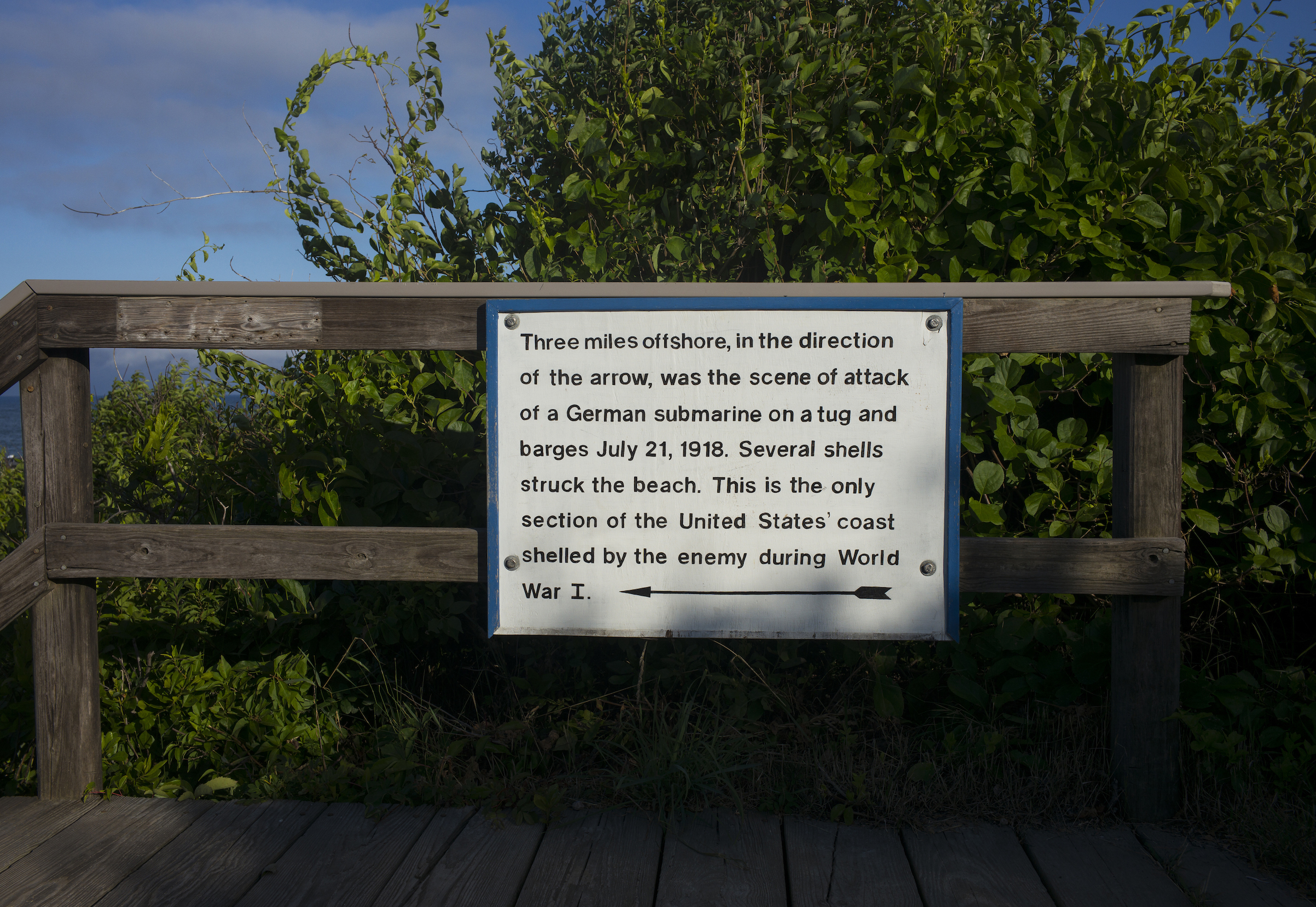 A sign describes where a German submarine three miles offshore on July 21, 1918, attacked a tug and barges and where artillery shells struck the beach below on NausettHeights in East Orleans, Mass. (Photographed in 2016)