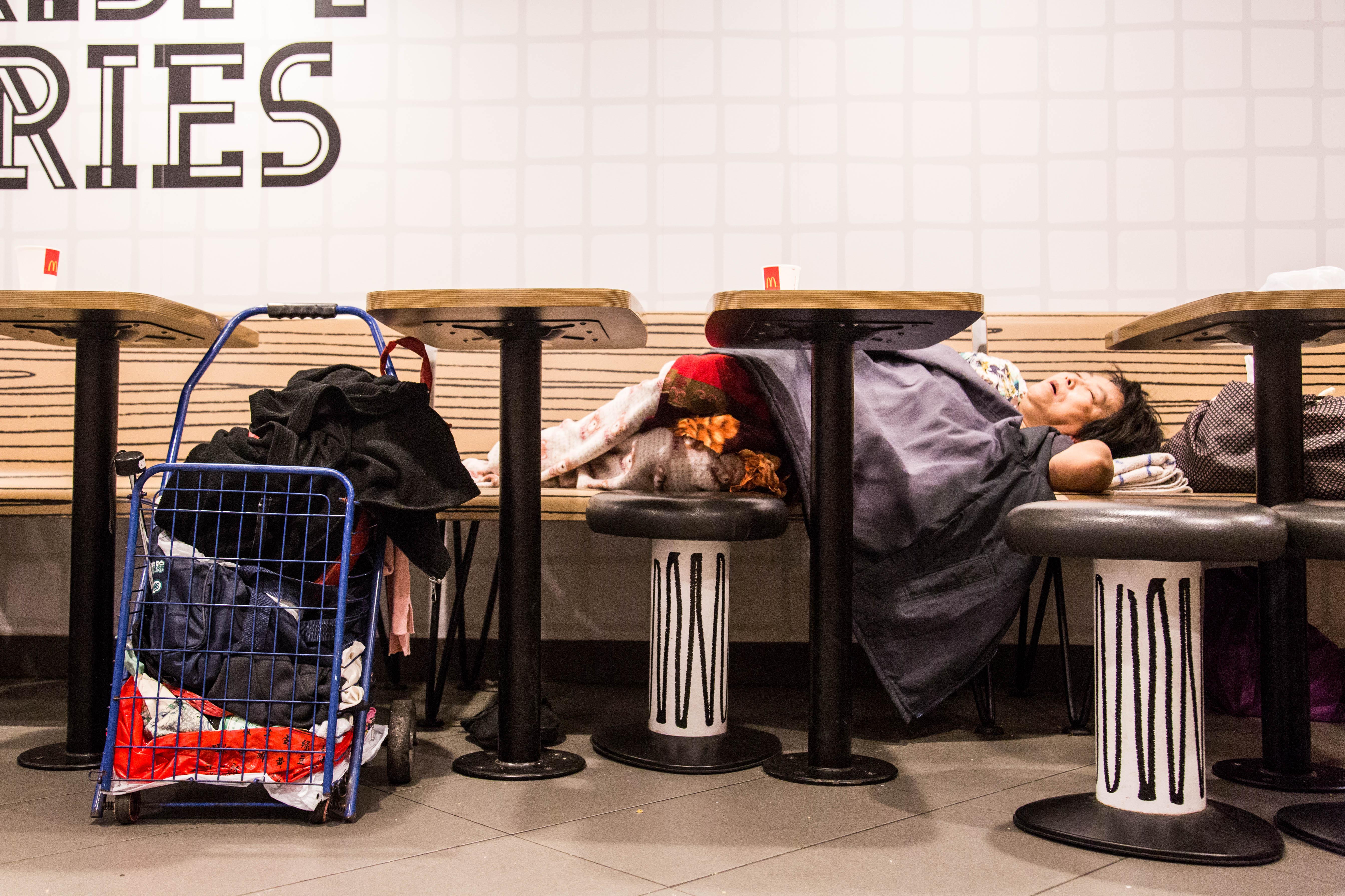 A 'McRefugee' sleeps in a restaurant in Hong Kong.