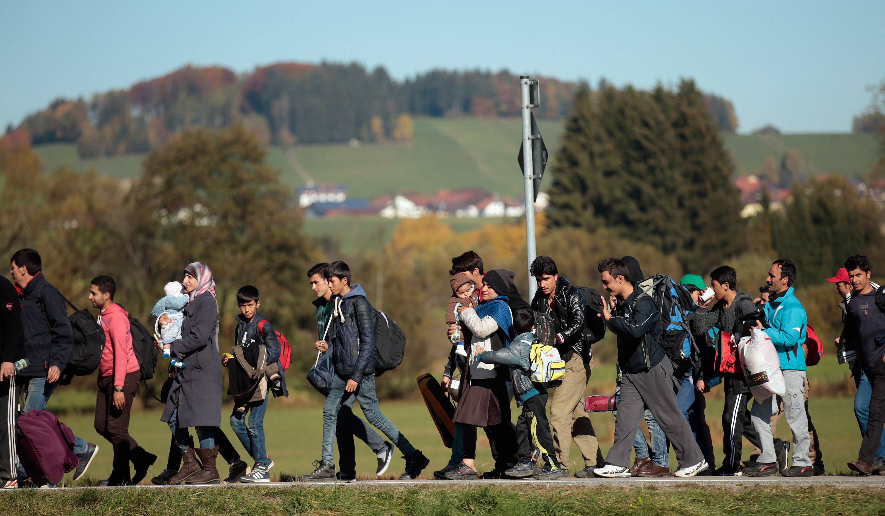 German police lead arriving migrants along a street to a transport facility after gathering them at the border to Austria on October 28, 2015 near Wegscheid, Germany.