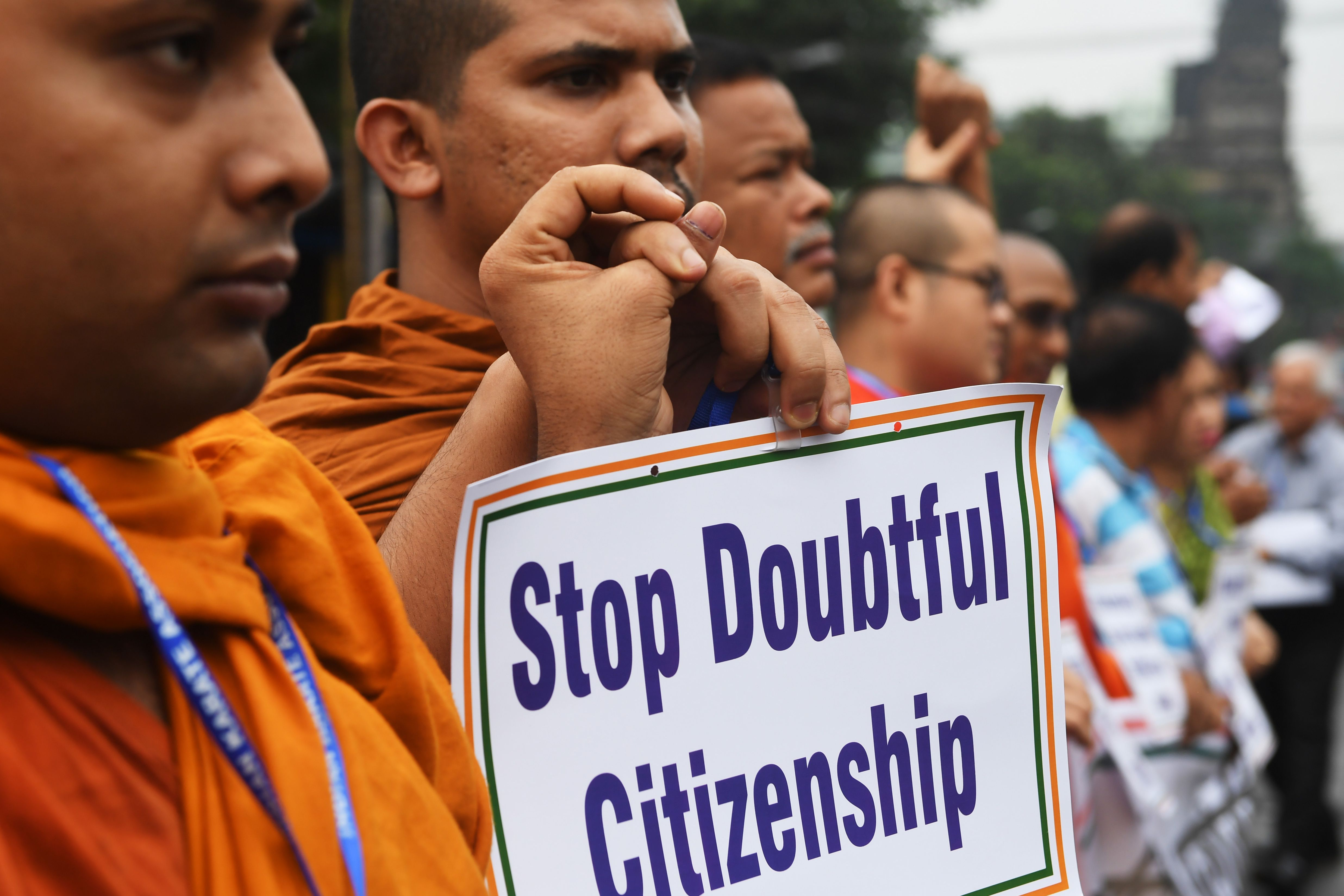 Social activists hold posters during a protest following the publication of a draft of the National Register of Citizens (NRC) in Kolkata on August 1, 2018.