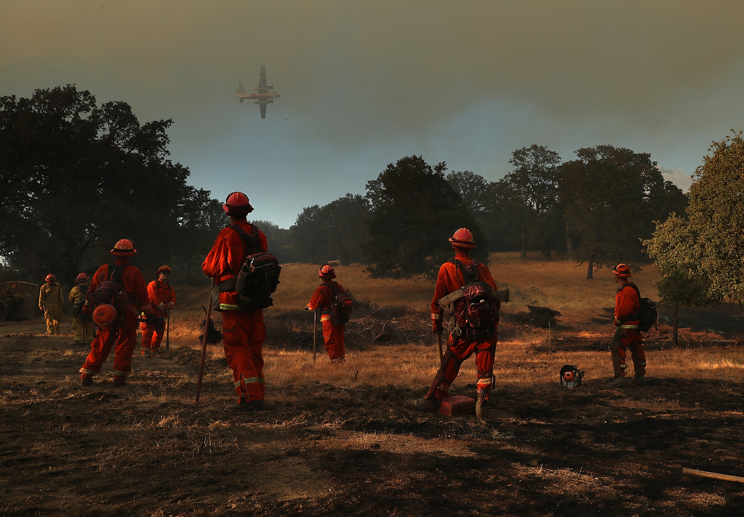 Inmate firefighters look on as a firefighting aircraft prepares to drop fire retardant ahead of the River Fire as it burns through a canyon in Lakeport, Calif. on on Aug. 1, 2018.