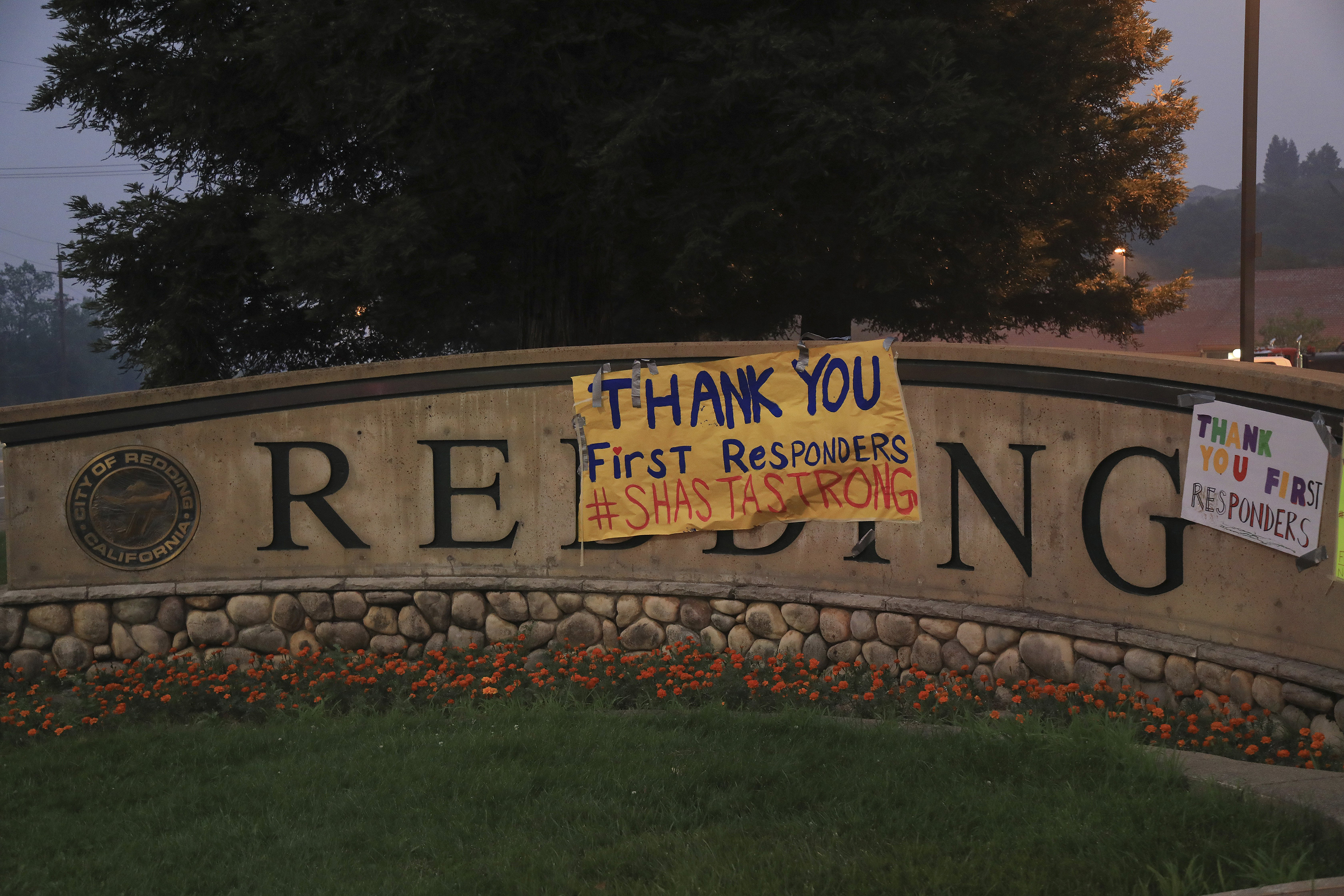 Signs of encouragement for first responders is hung on a city sign in Redding, Calif., July 31.
