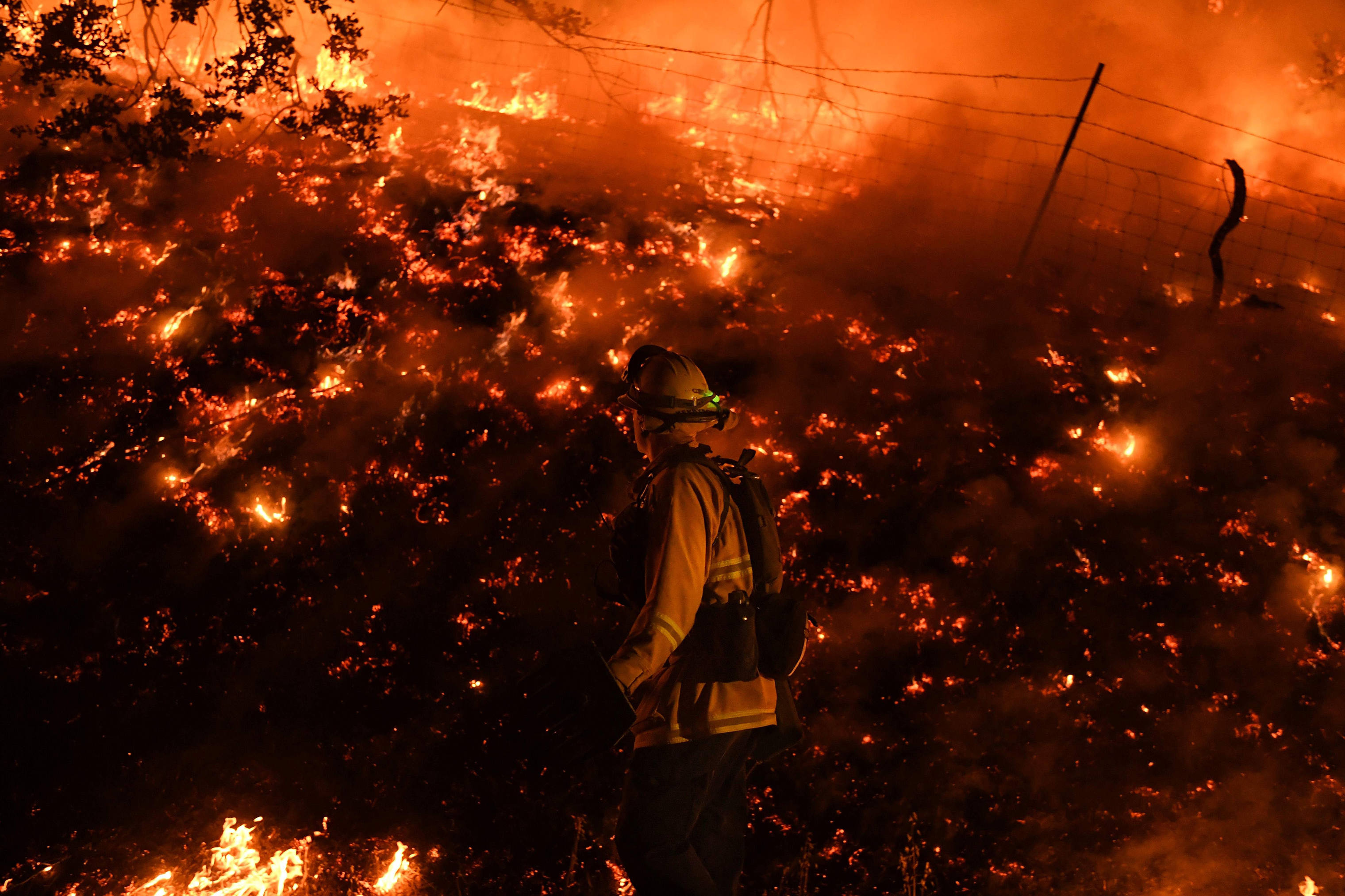 Firefighters conduct a controlled burn to defend houses against flames from the Ranch fire, as it continues to spreads towards the town of Upper Lake, Calif. on Aug. 2.