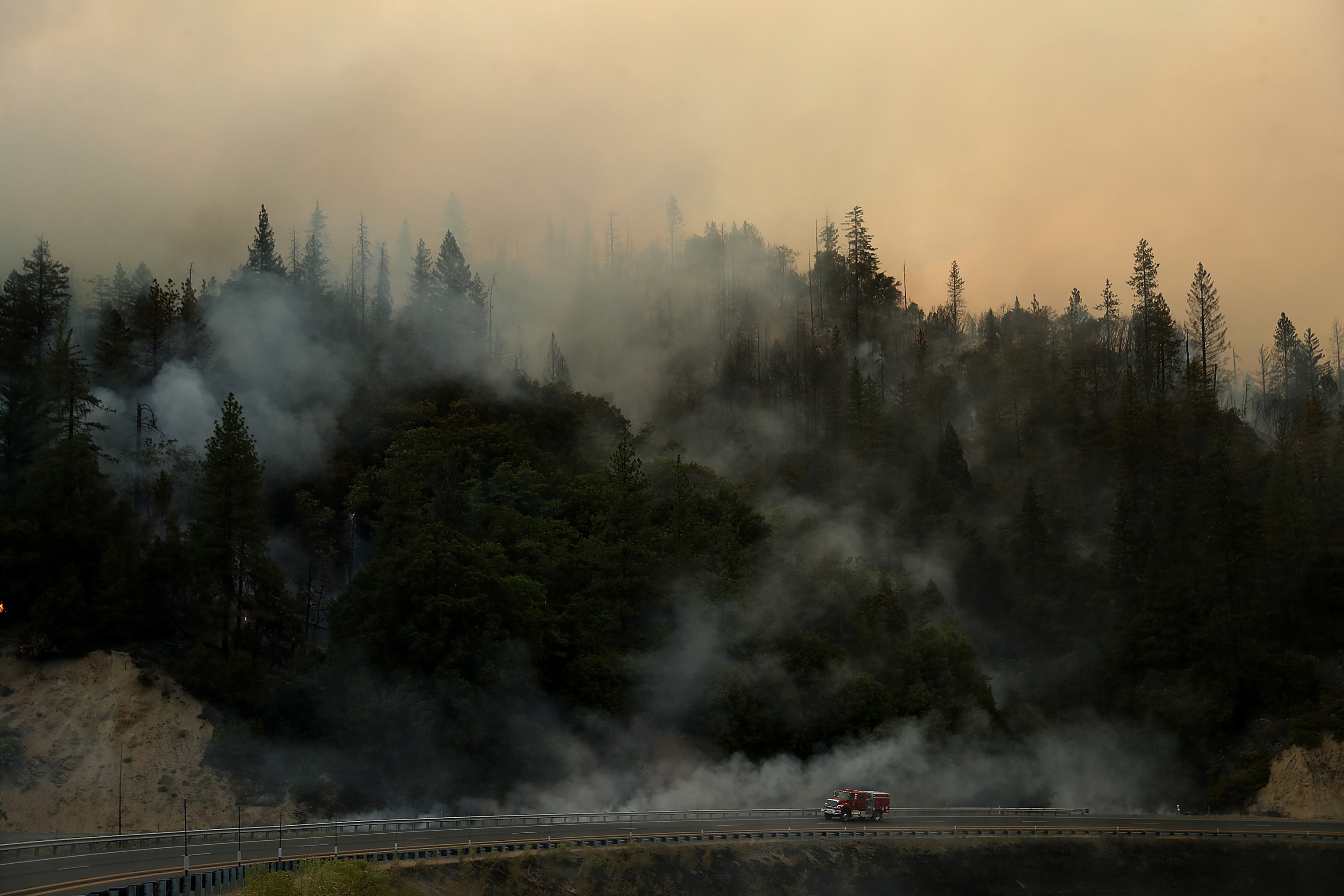 A Cal Fire truck drives along highway 299 as the Carr Fire burns in the hills near Whiskeytown, Calif. on July 28.