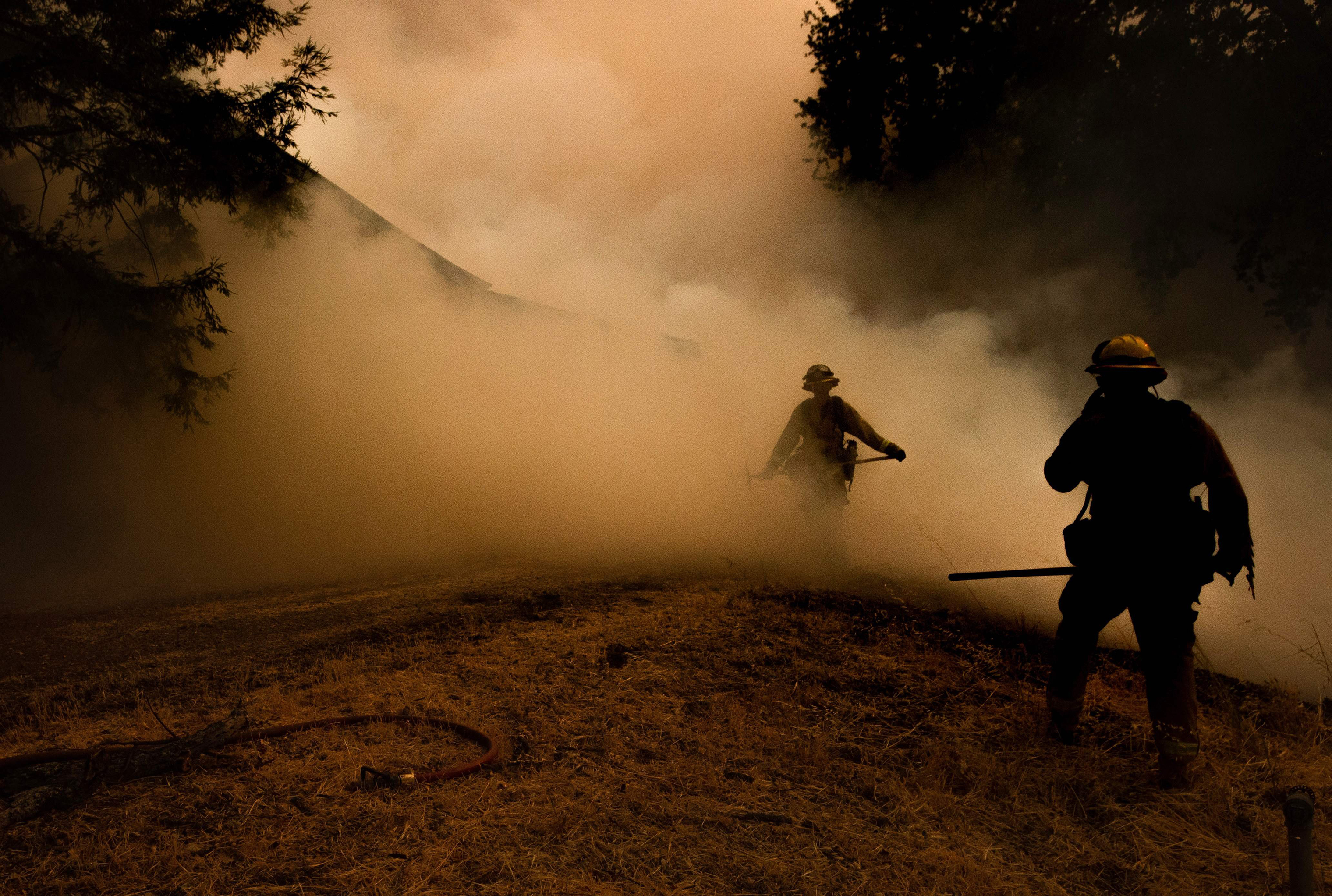 A firefighter walks through smoke as flames approach a home during the Mendocino Complex fire in Lakeport, Calif. on July 30.