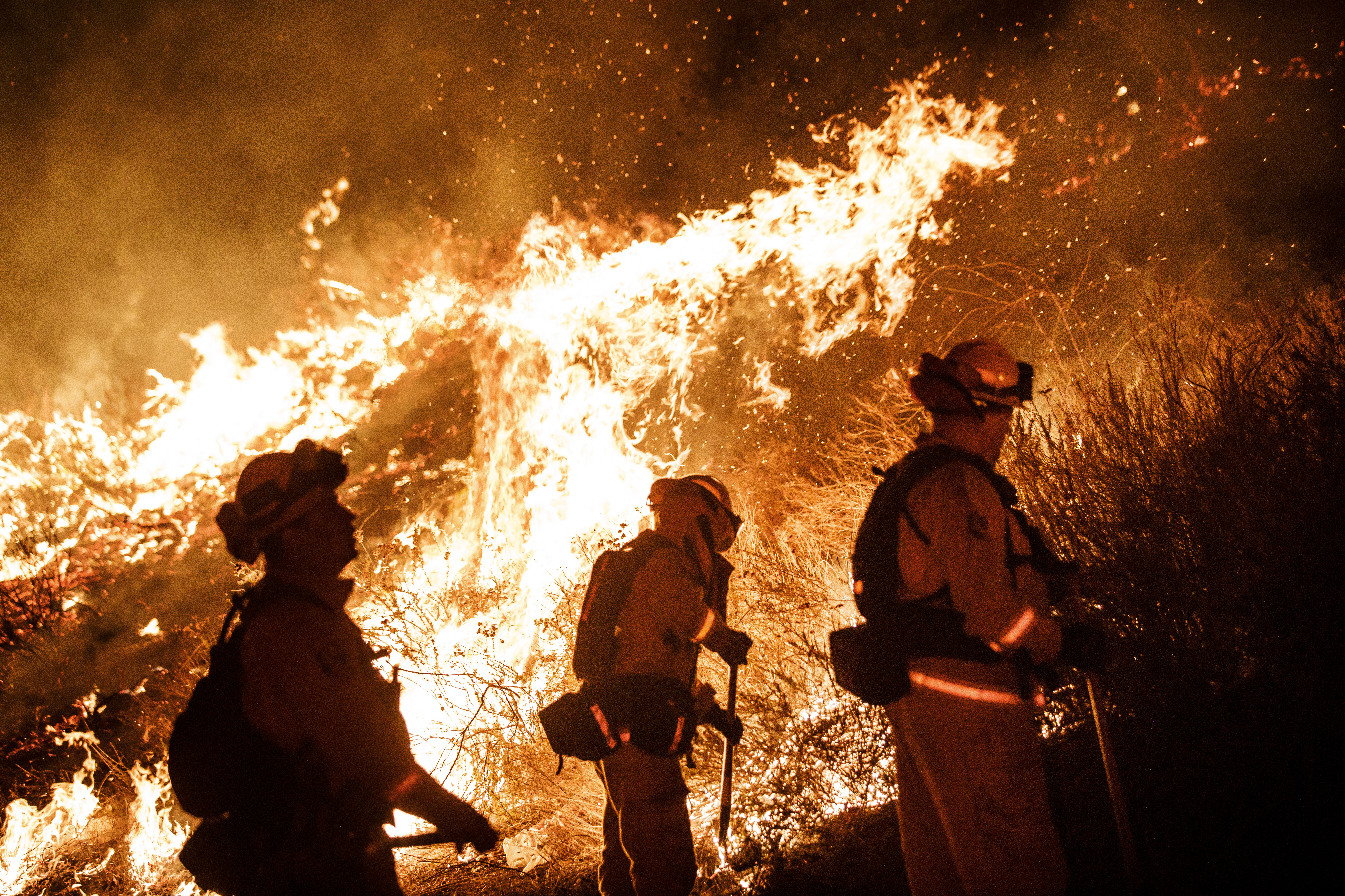 Firefighters conduct a burn operation to remove fuel around homes on Grand Ave as the Holy Fire grows to more than 10,000 acres as the wildfire comes closer to Lake Elsinore, Calif., on Aug. 10, 2018.