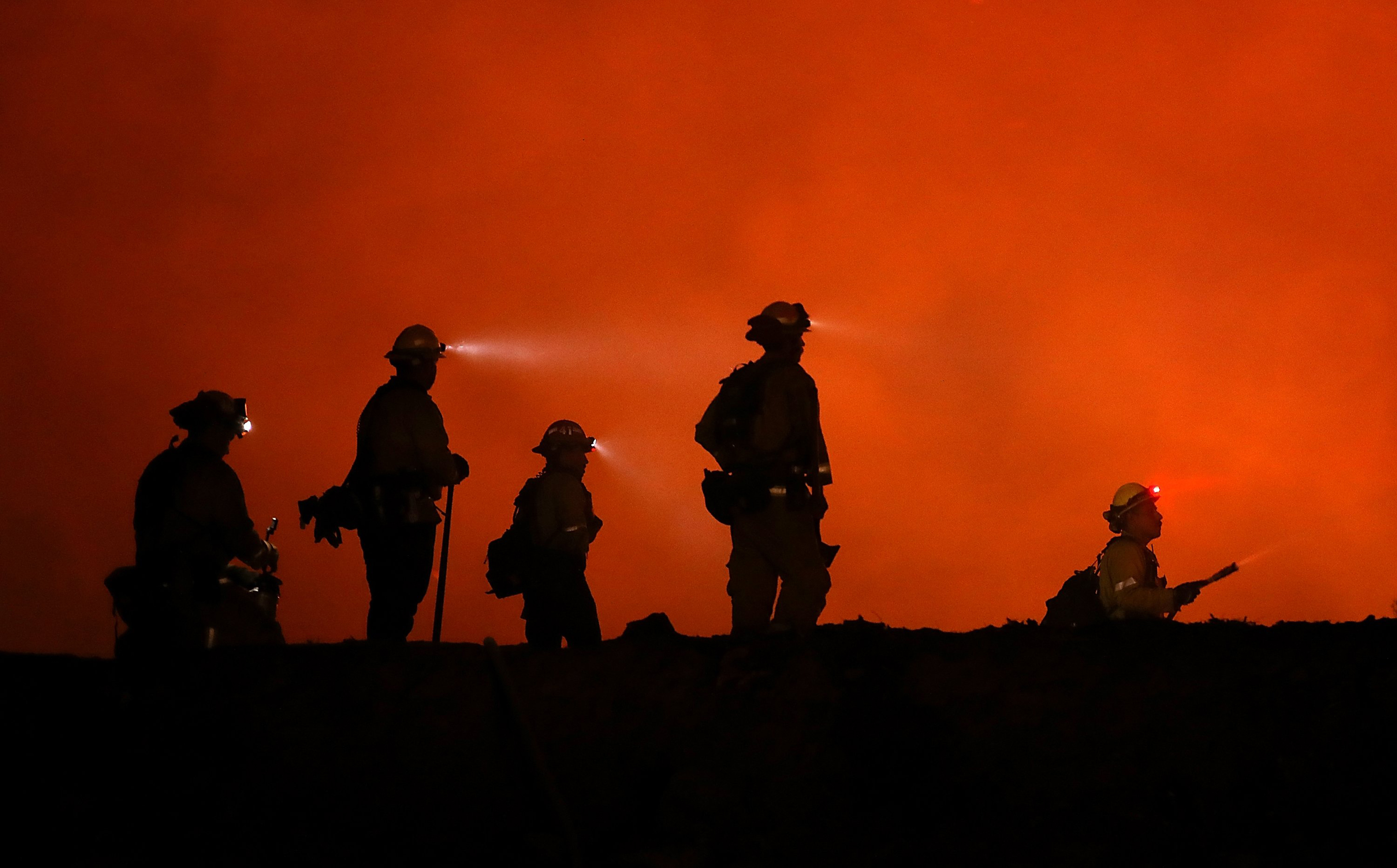 Cal Fire firefighters monitor a back fire as they battle the Medocino Complex fire near Lodoga, Calif. on Aug. 7.