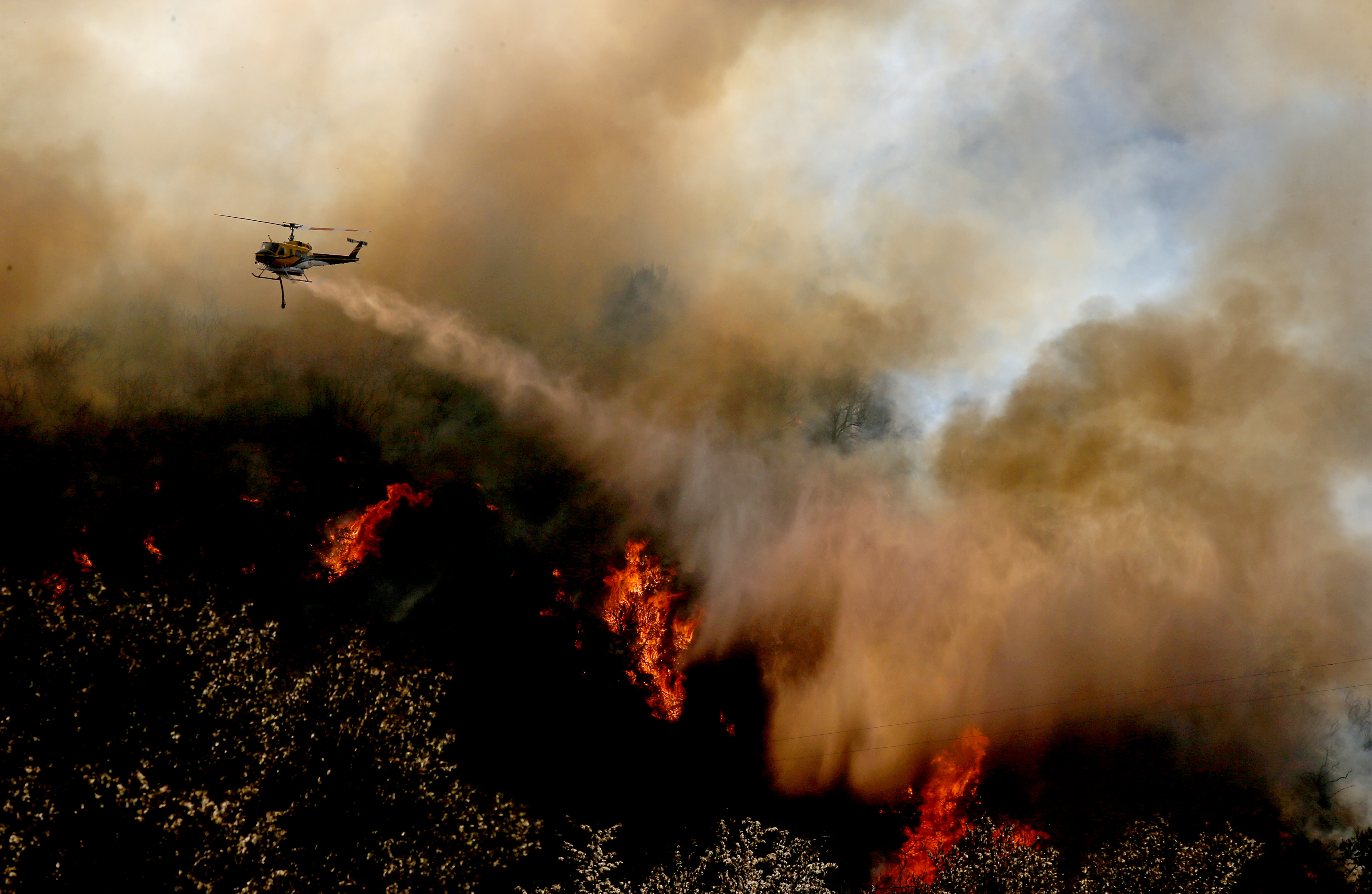 A firefighting helicopter makes a water drop on a flare-up of the Blue Cut fire along Interstate 15 in the Cajon Pass on Thursday, Aug. 18, 2016.