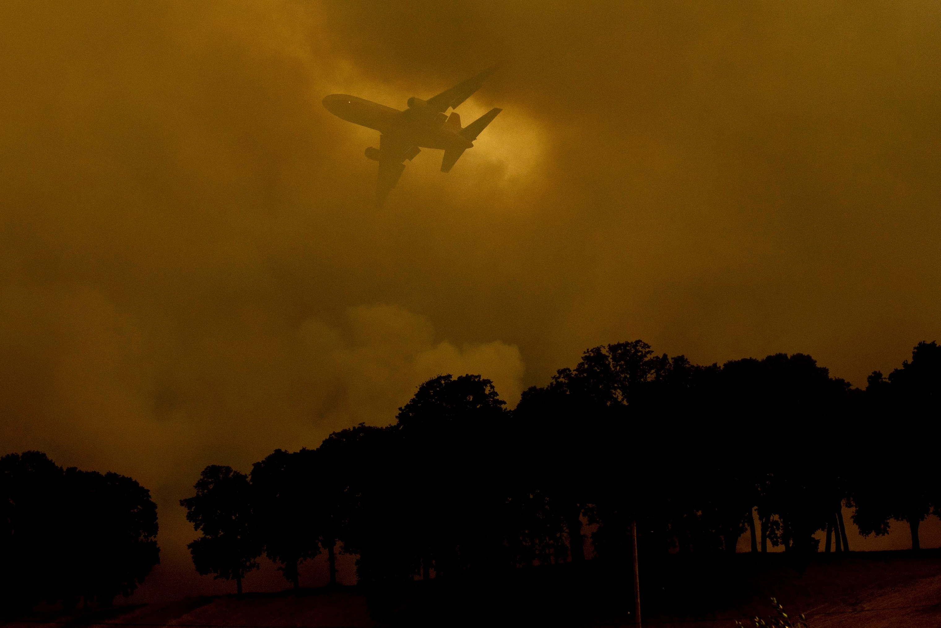 An air tanker passes behind a smoke plume while battling the River Fire in Lakeport, Calif. on July 30.