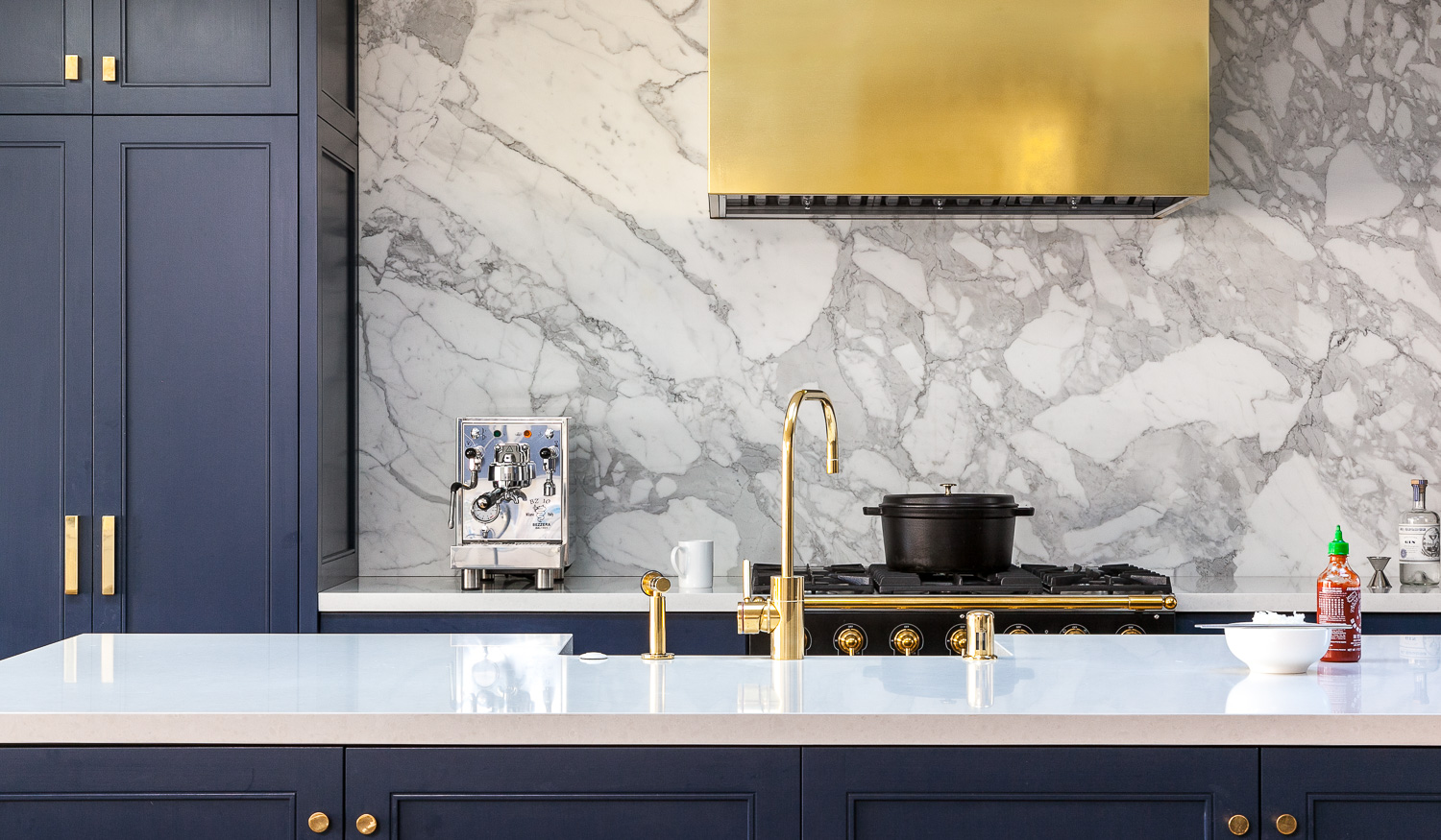 A kitchen with a custom metallic hood designed by interior designer Grant K. Gibson.