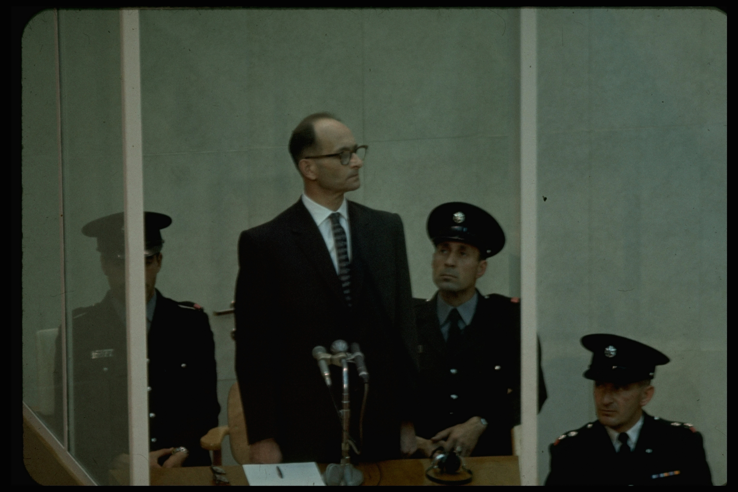 Nazi Adolf Eichmann standing in prisoner's cage during reading of indictment against him at his trial for war crimes, in 1961.