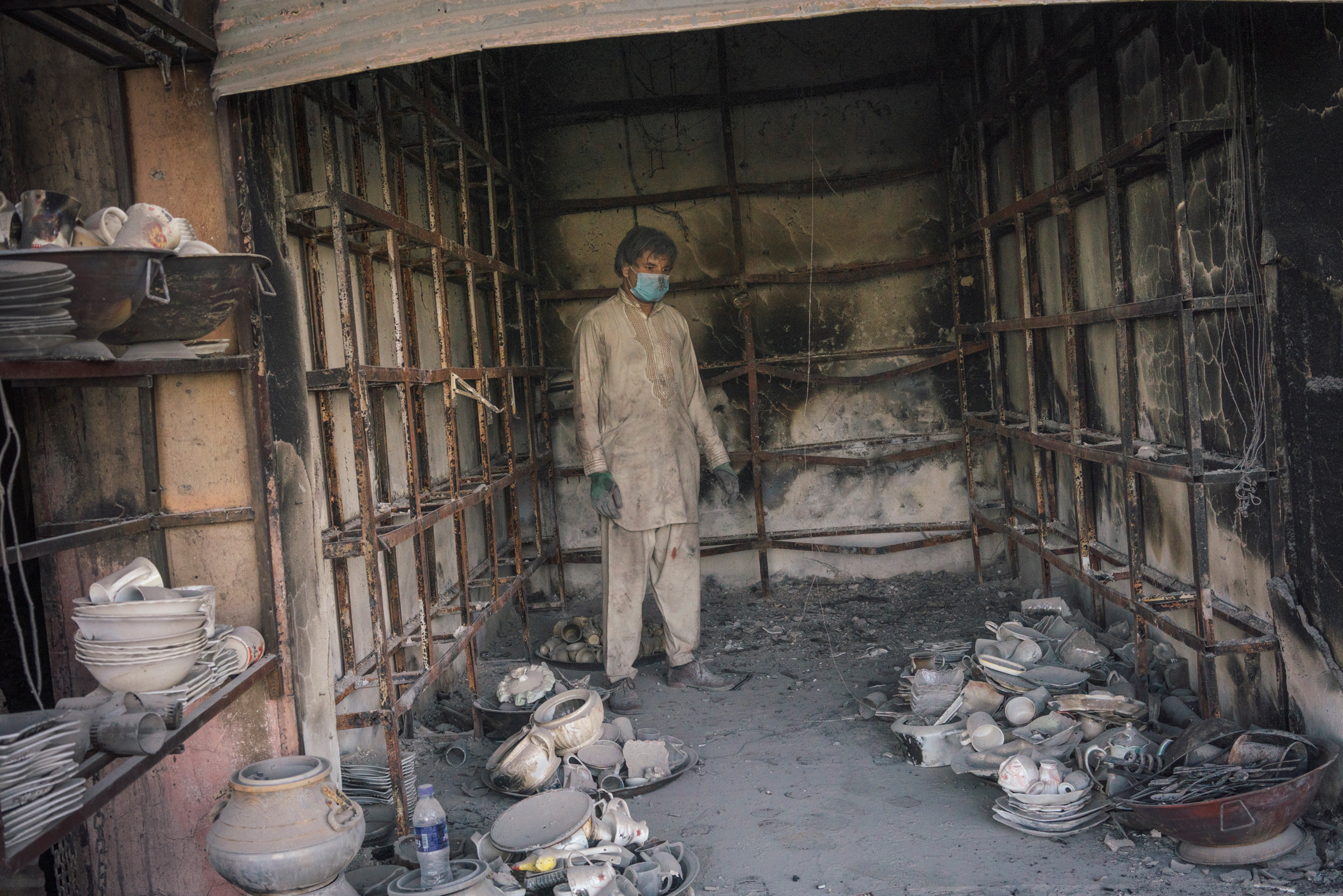 Nassarath Kadri, 27, inside his damaged shop in Ghazni on Aug. 16.