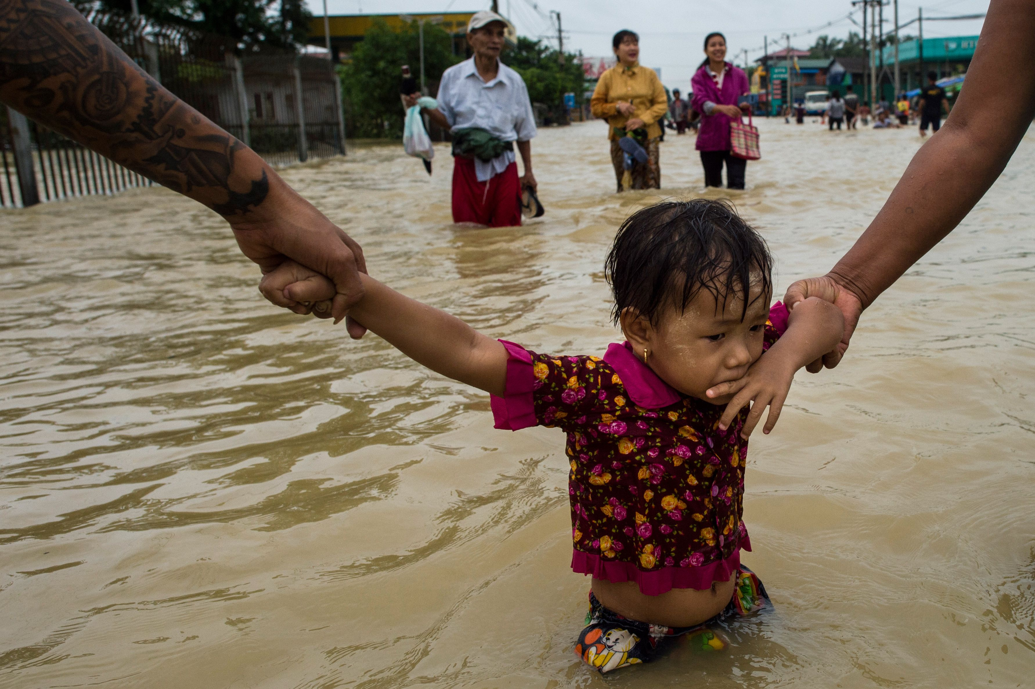 Residents hold onto a child as they walk through floodwaters in the Bago region, some 68 km away from Yangon, on July 29, 2018.