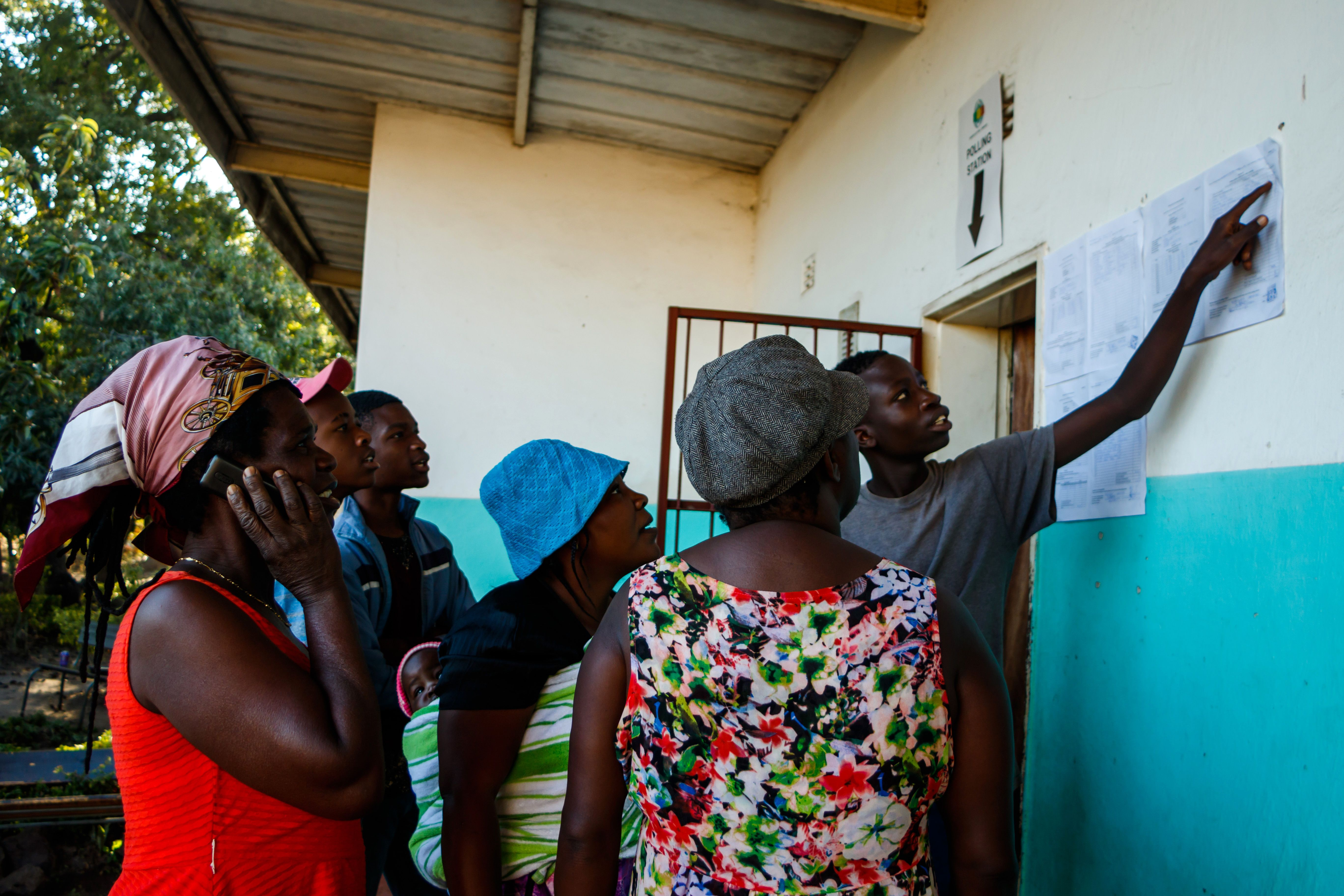 People gather a day after elections to look at results posted outside a polling station in Harare, Zimbabwe on July 31 2018.