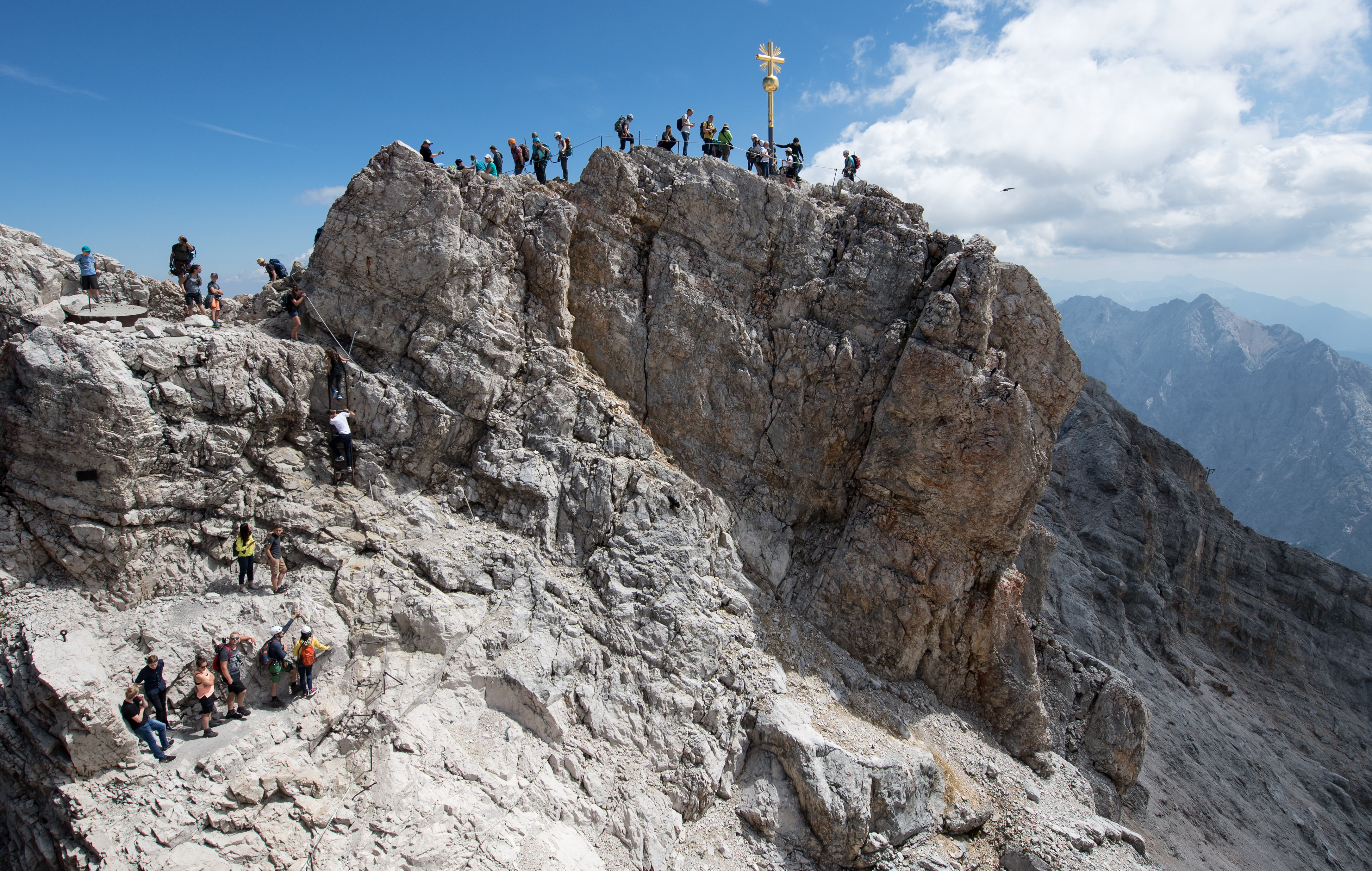 Numerous excursionists use the beautiful weather for an excursion to the summit cross on the Zugspitze.