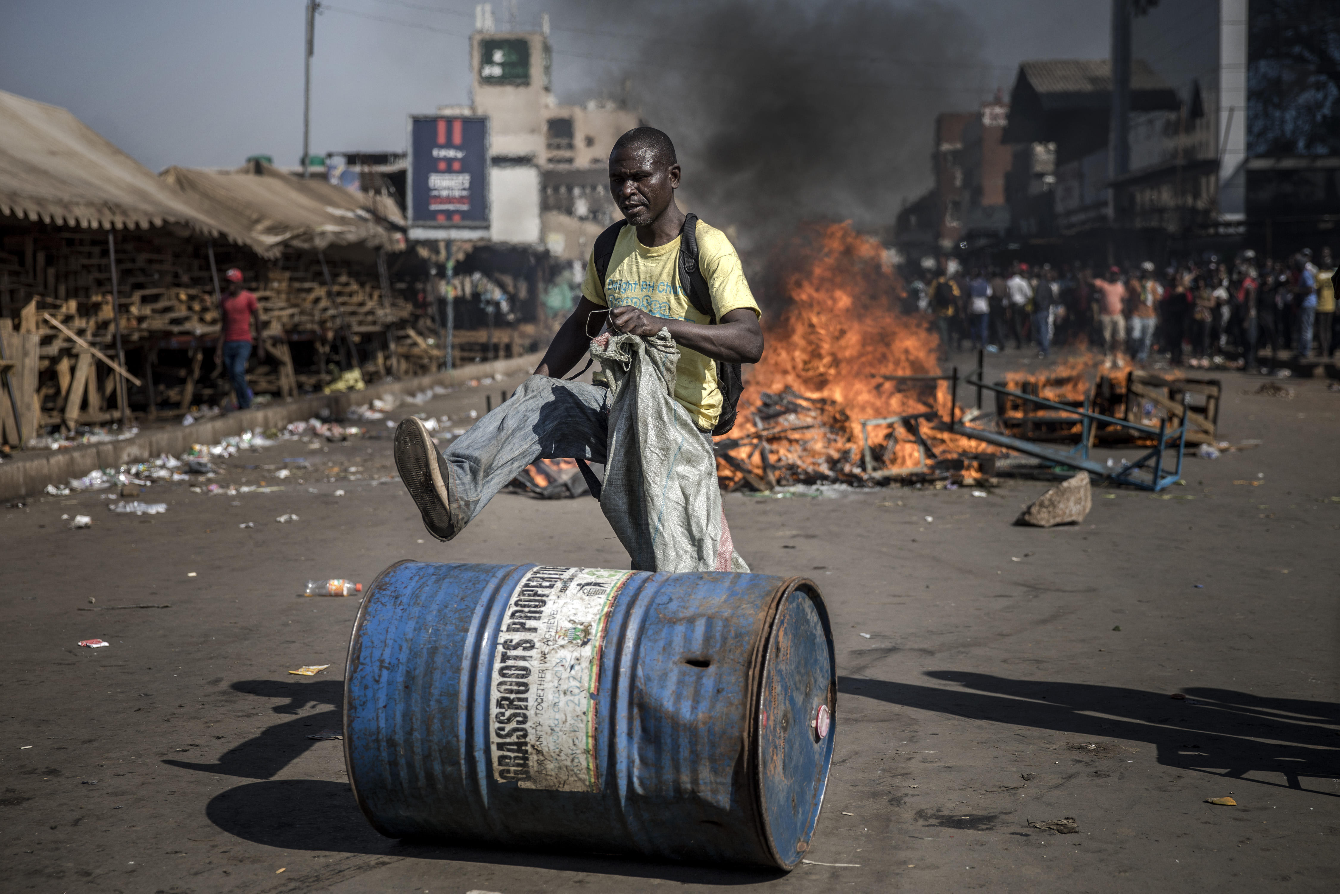 A man walks over a barrel in front of a fire in Harare on August 1, 2018, as protests erupted over alleged fraud in Zimbabwe's election.
