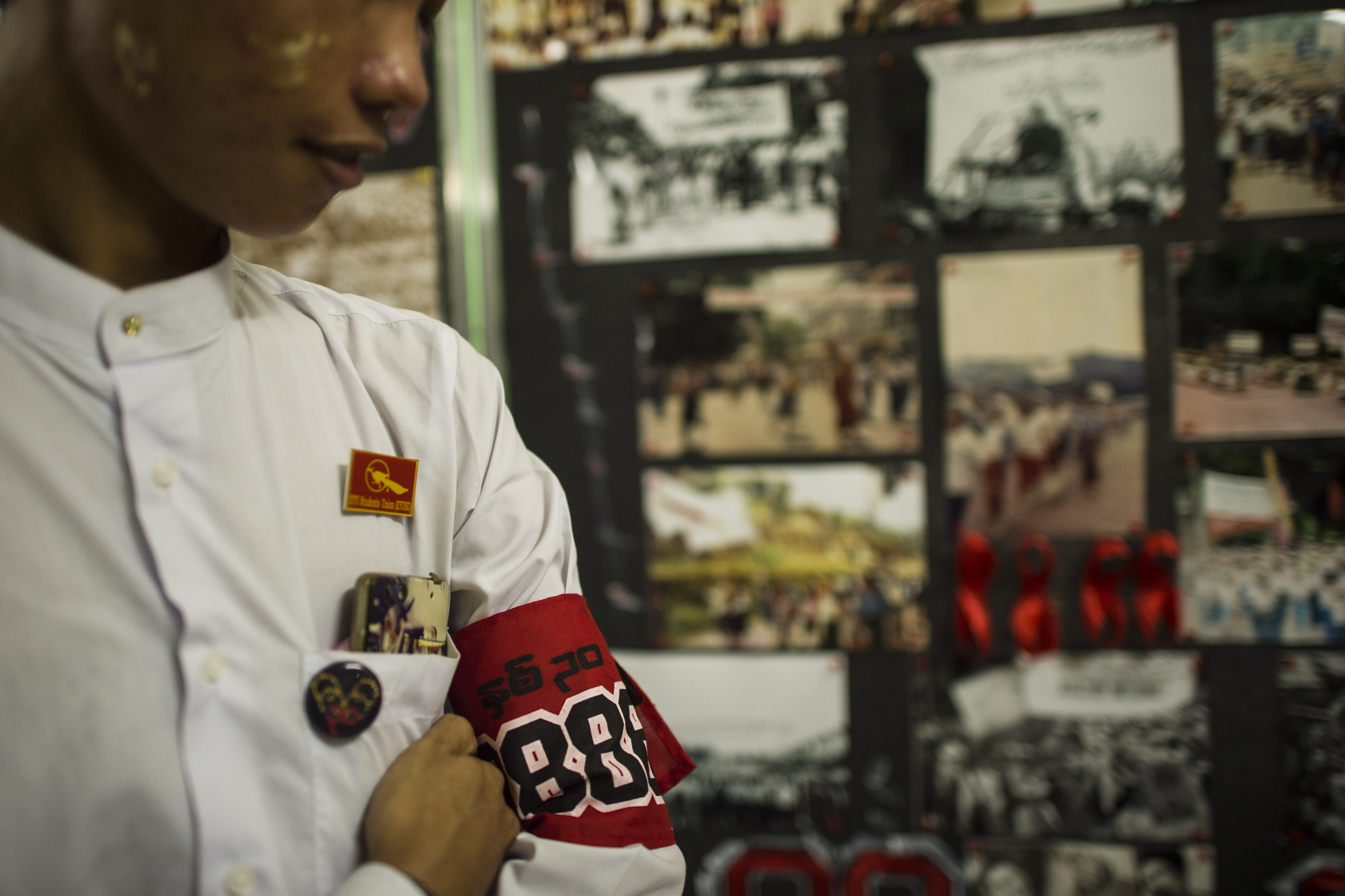 A student wearing an armband stands next to a photo exhibition held as part of events to commemorate the 30th anniversary of the 8888 Uprising at the University of Yangon on Aug. 6, 2018.