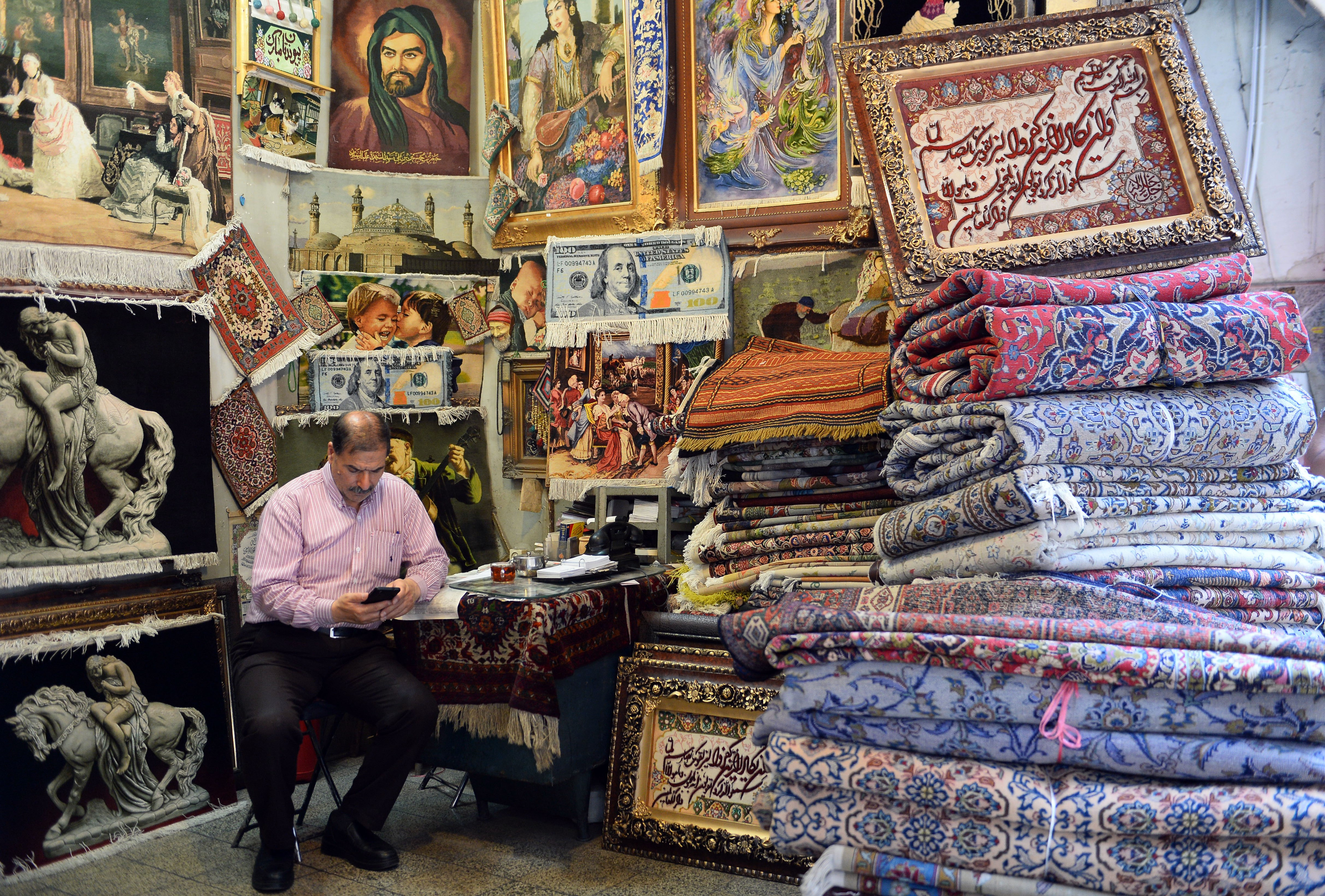 A carpet seller is seen at a bazaar in Tehran a day before the U.S. re-enforced sanctions against Iran on Aug. 7, 2018