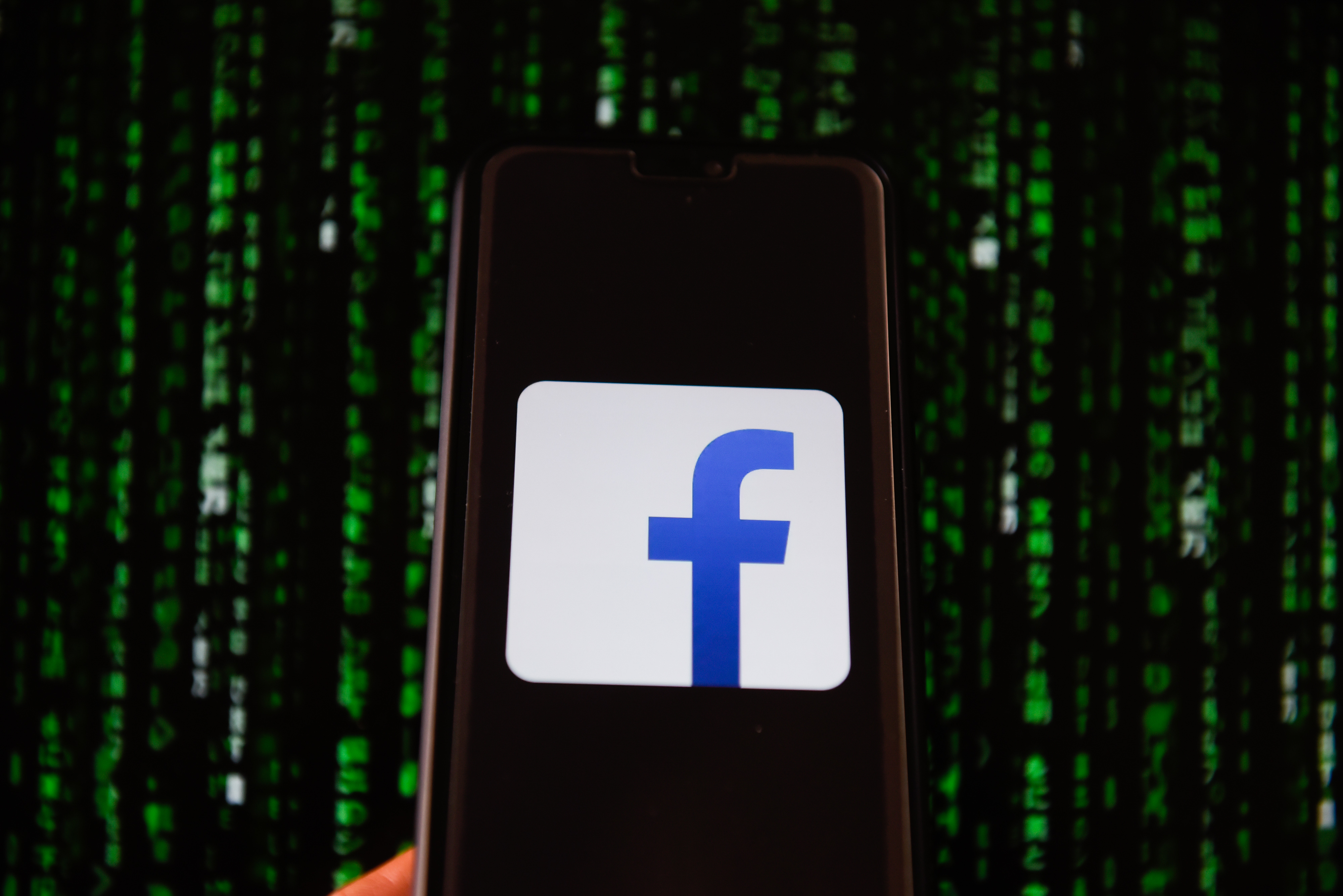 Facebook logo is seen on a mobile phone.