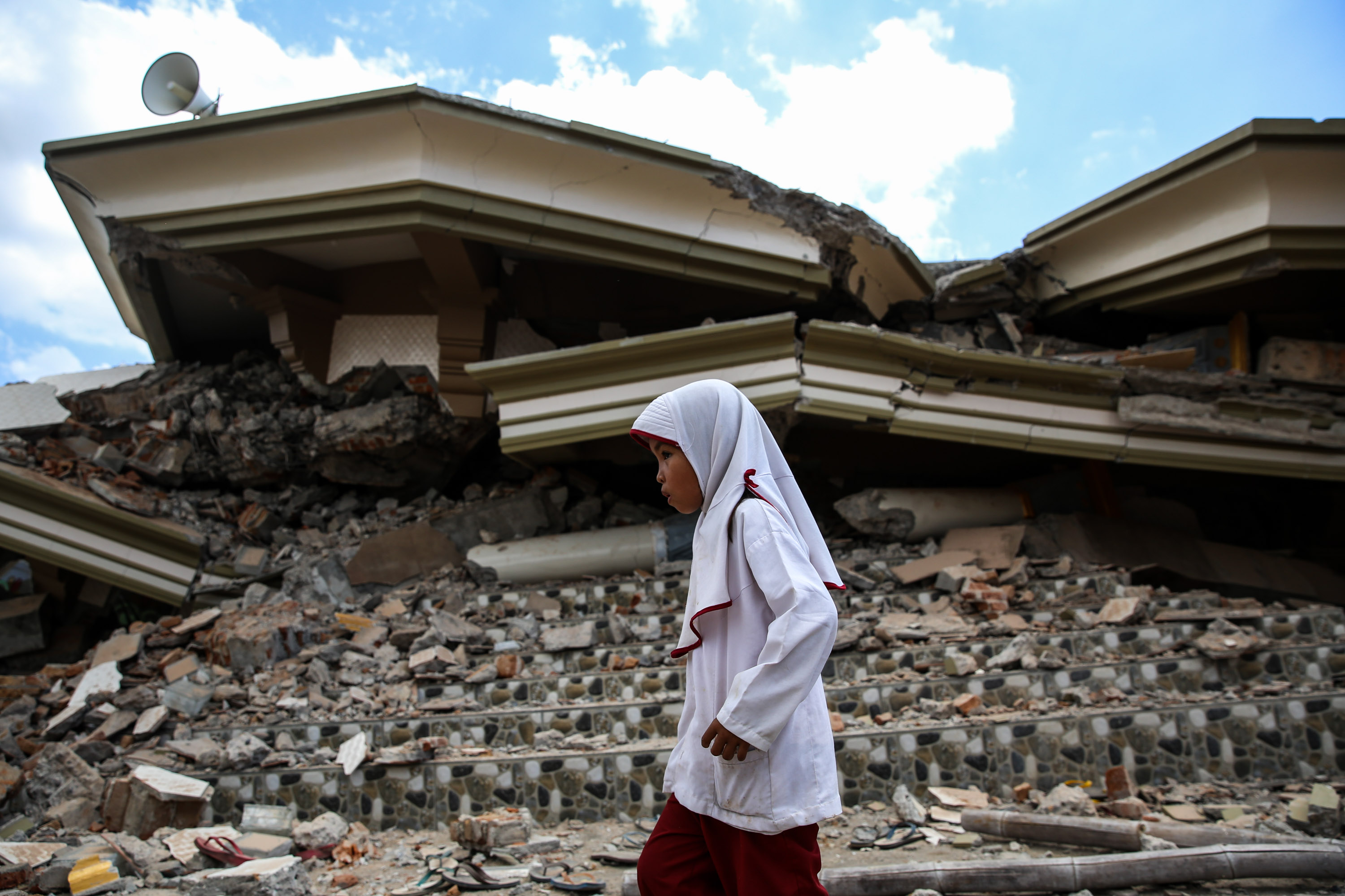 A girl stands next to a collapsed mosque after an earthquake in North Lombok, Indonesia on Aug. 7, 2018.