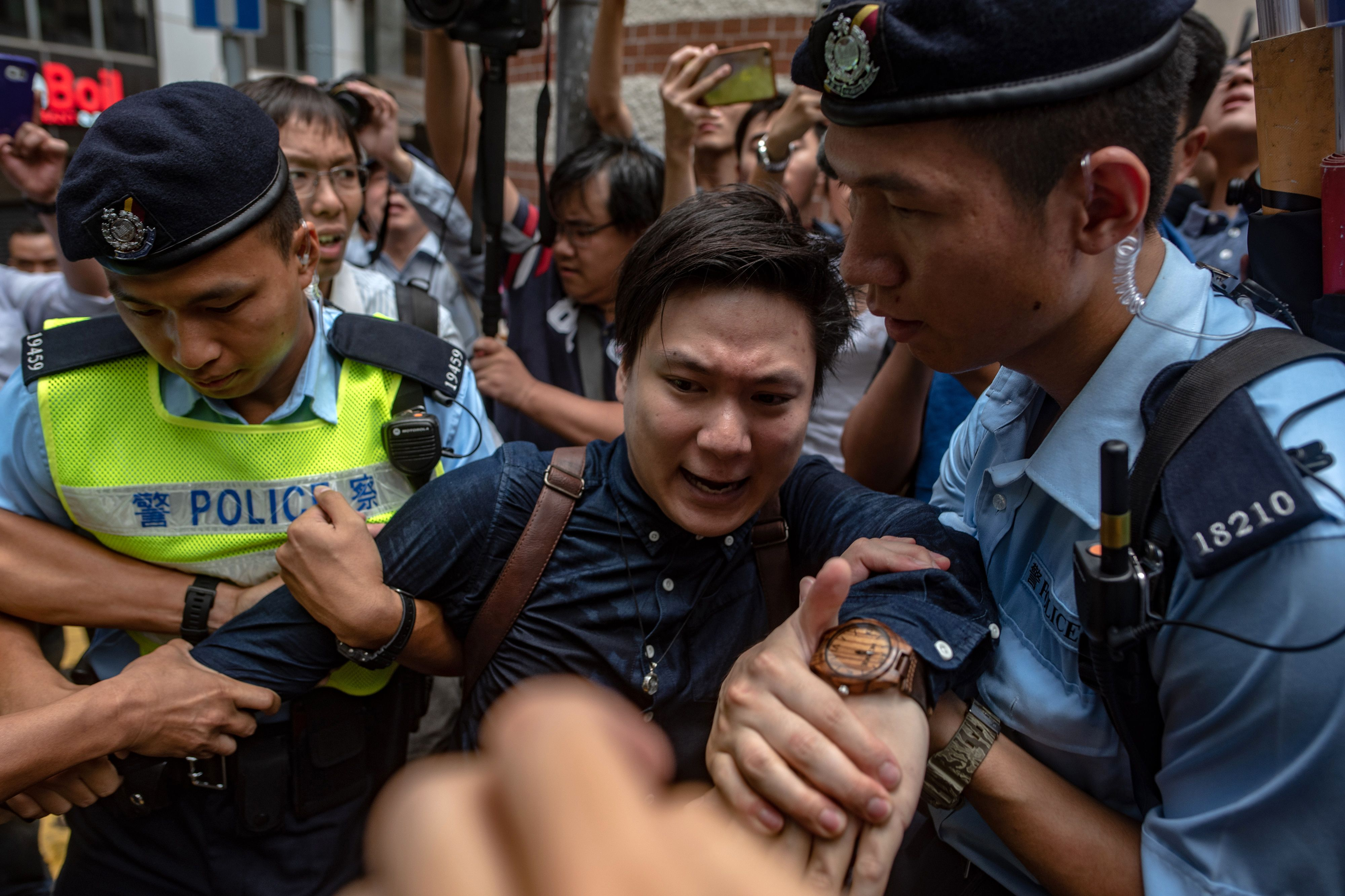 Pro-independence activist Wayne Chan is removed by police from a location outside the Foreign Correspondents' Club (FCC), as people protest ahead of a speech by pro-independence activist Andy Chan, in Hong Kong on August 14, 2018.