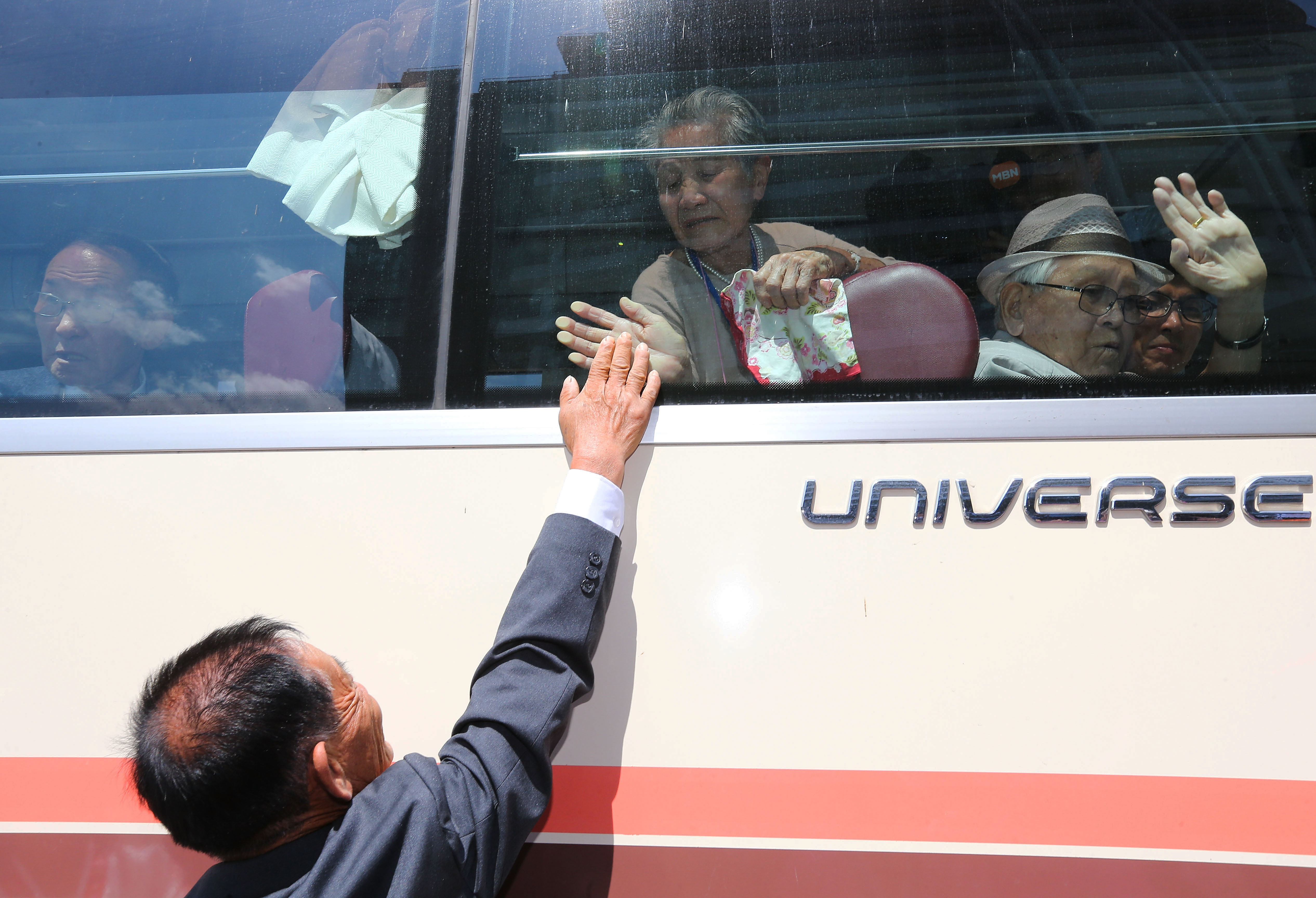 South Korean Lee Geum-Sum, 92 (in bus) waves to her North Korean son Lee Sung-Chul, 71, at the end of a three-day family reunion meeting in Mount Kumgang, North Korea on Aug. 22, 2018.