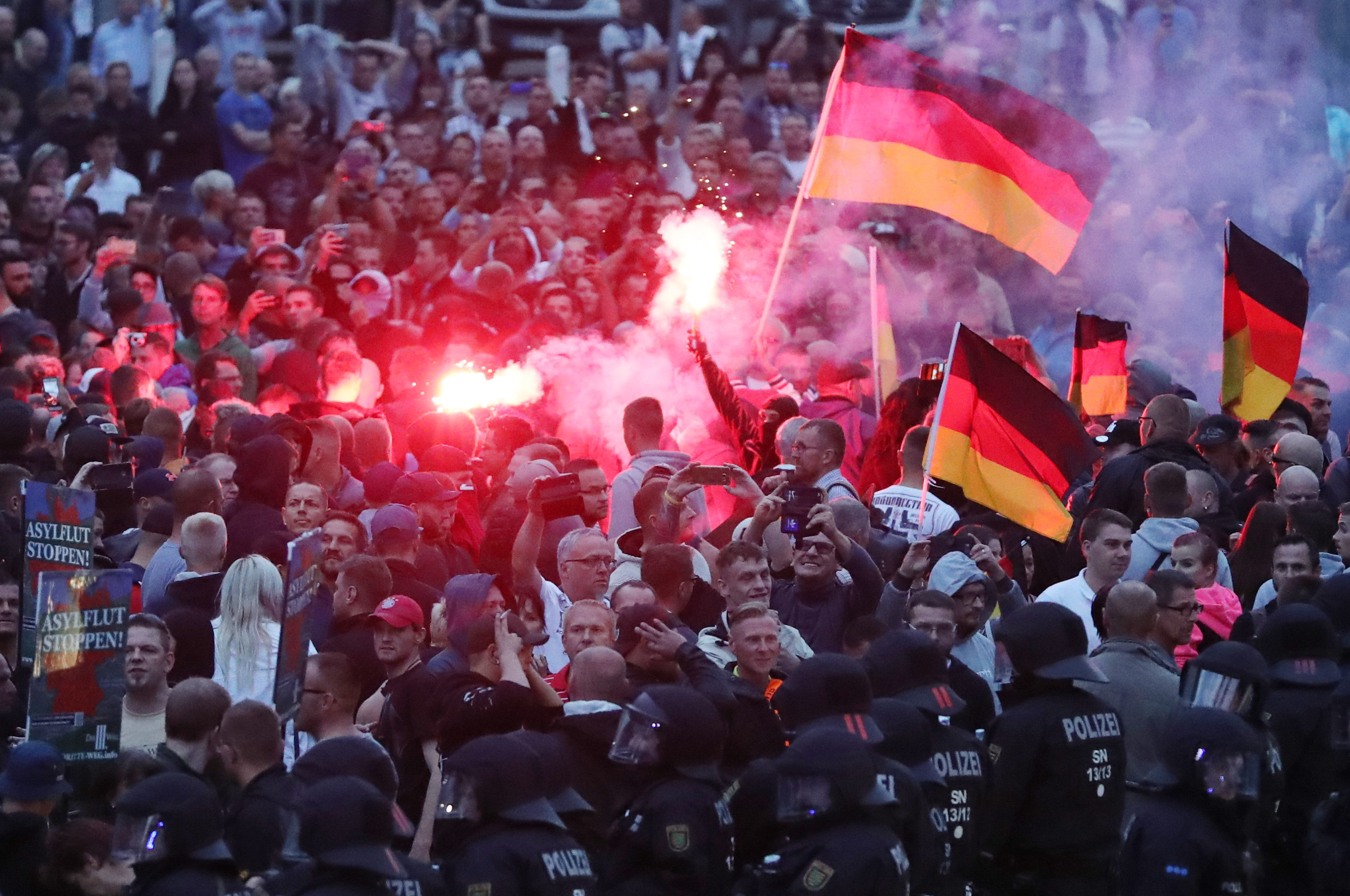 Right-wing demonstrators ignite pyrotechnics and wave German flags in Chemnitz, at a protest against migration following the stabbing of a local man, over which an Iraqi and a Syrian were arrested.