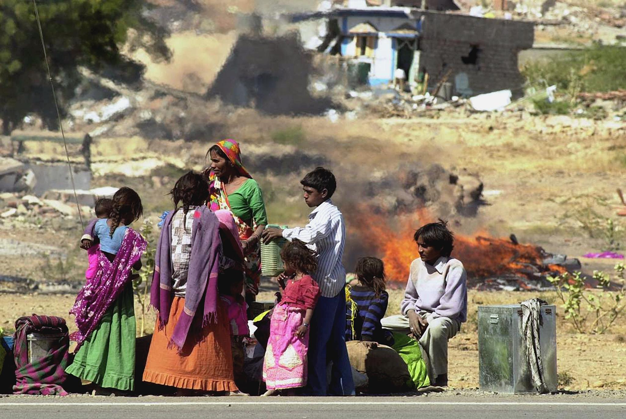 A homeless family waits for a vehicle on Jan. 27, 2001 against a backdrop of ruined houses and a funeral pyre, in the village of Boundi in Bhuj district in Gujarat.