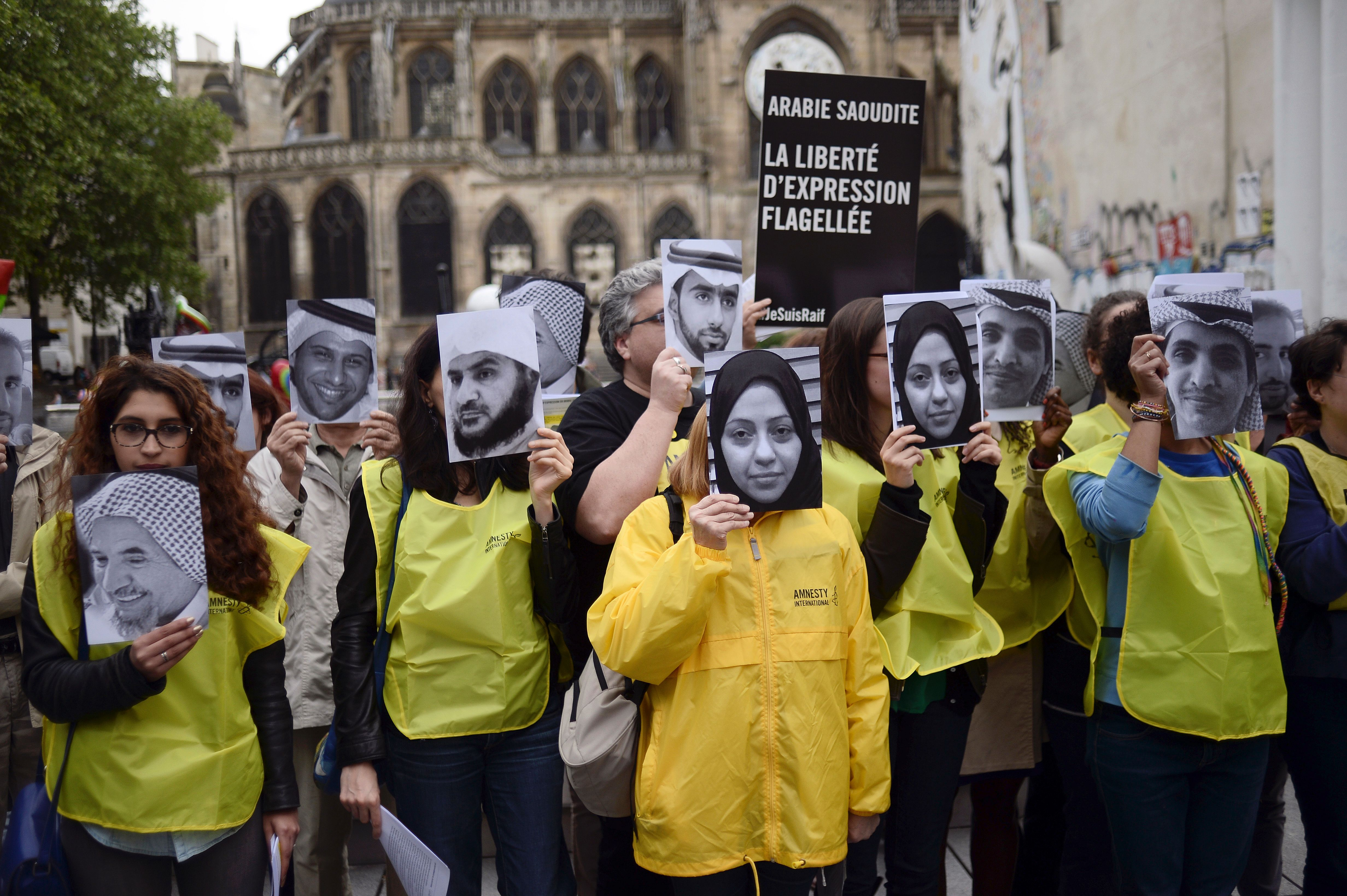 People hold pictures of Samar Badawi and her brother jailed Saudi blogger Raif Badawi, who was sentenced to 1,000 lashes for  insulting Islam, on May 7, 2015 in Paris, France.