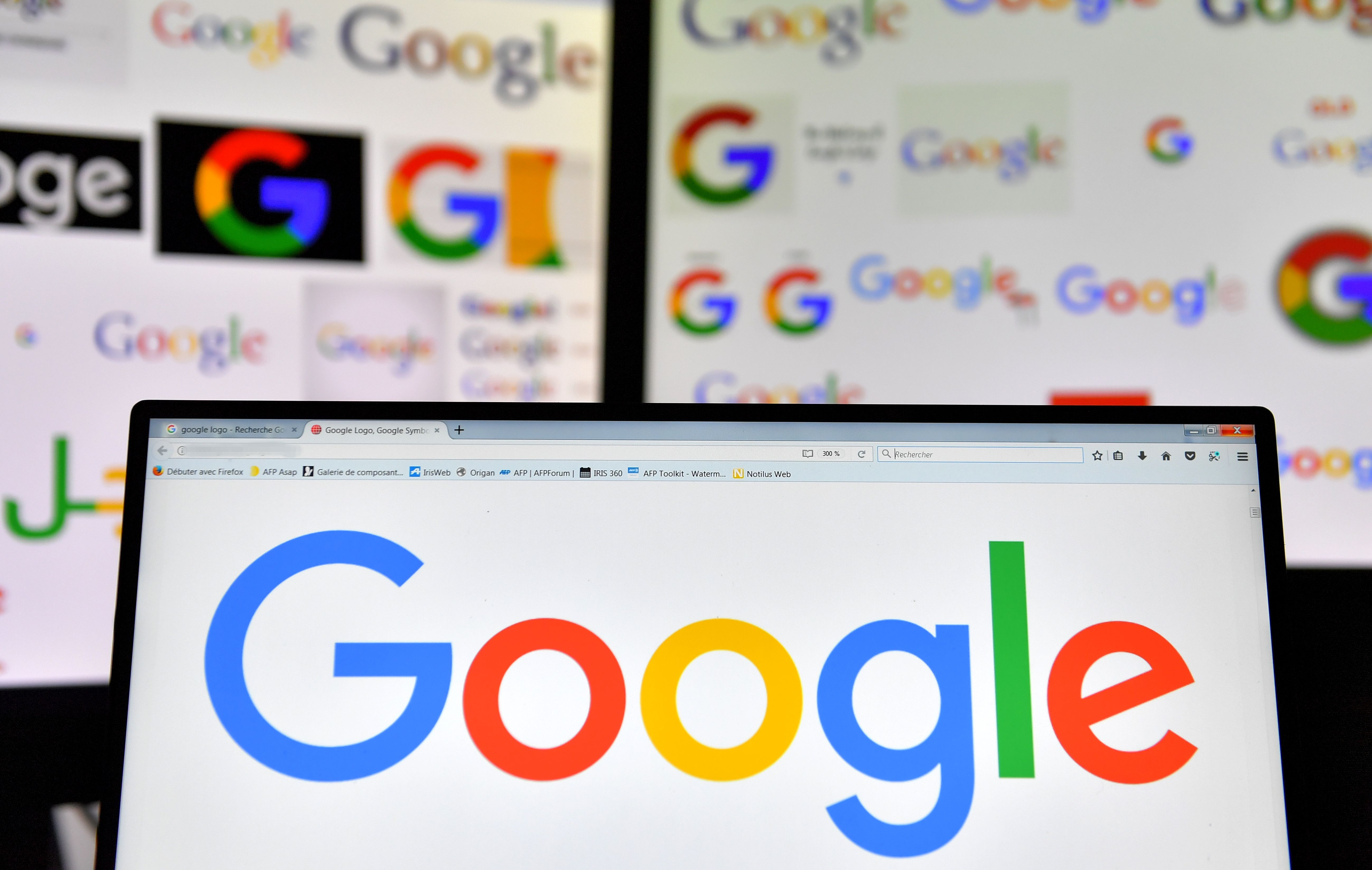 Google's logo is seen displayed on computer screens.