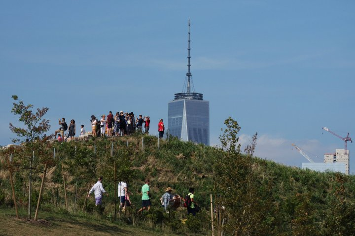 People climb The Hills on Governor's Island in front of One World Trade Center in New York City
