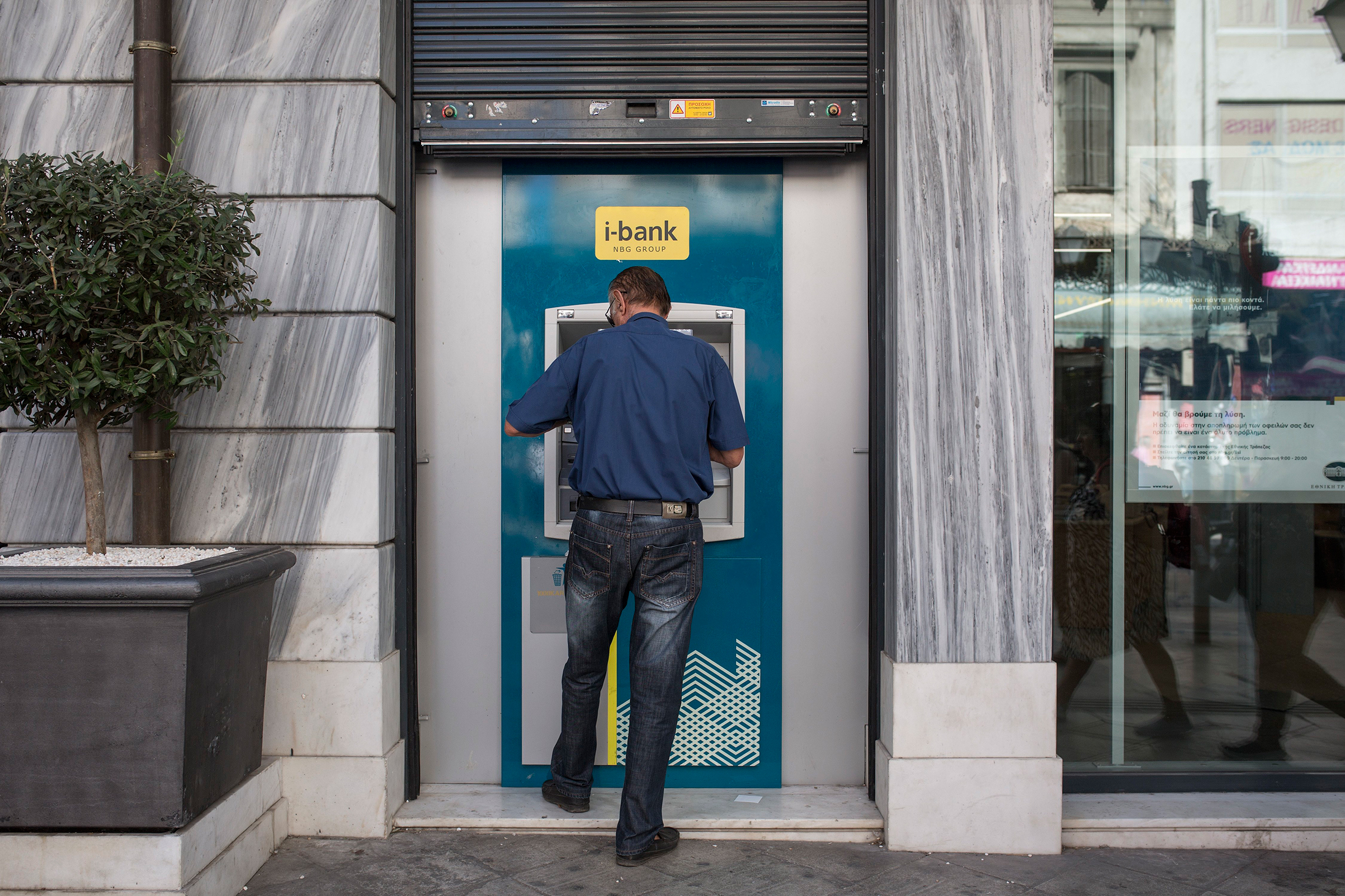 A man stands at an ATM in Athens. On Aug. 20, the last bailout program for Greece came to an end