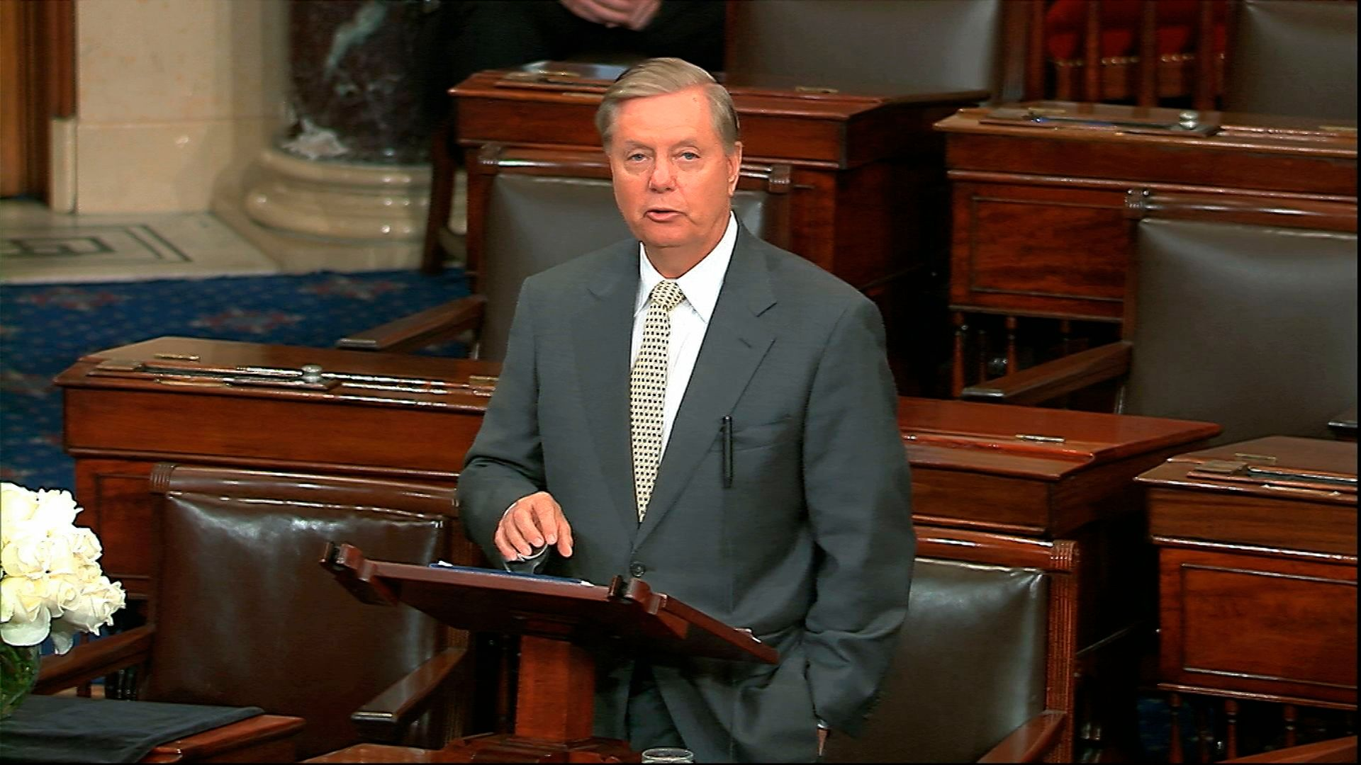 In this image from Senate Television, Sen. Lindsey Graham, R-S.C., speaks on the Senate floor at the Capitol in Washington,, next to the desk of Sen. John McCain, R-Ariz., draped in black with a bowl of white roses sitting on it on Aug. 28, 2018.
