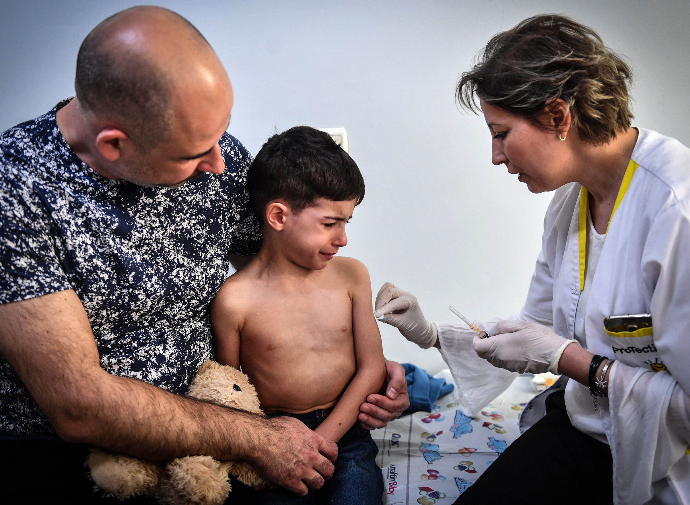 A child receives a vaccination against measles by a family physician on April 16, 2018 in the Romanian capital, Bucharest in Europe.