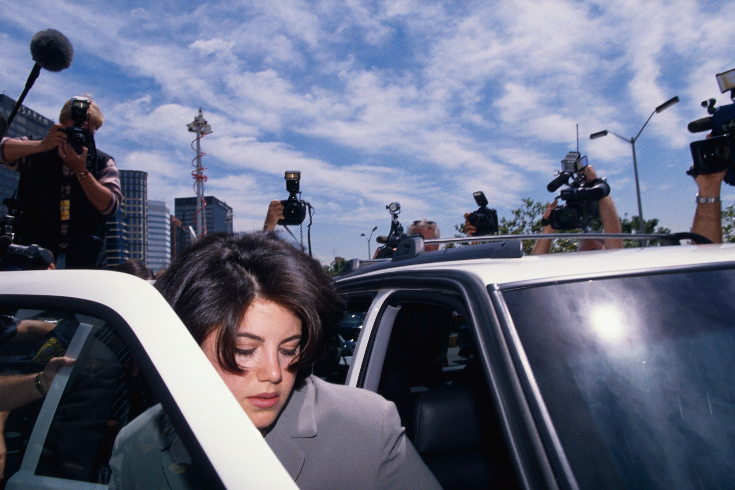 Monica Lewinsky is surrounded by photographers as she gets into car to go to the FBI Headquarters.