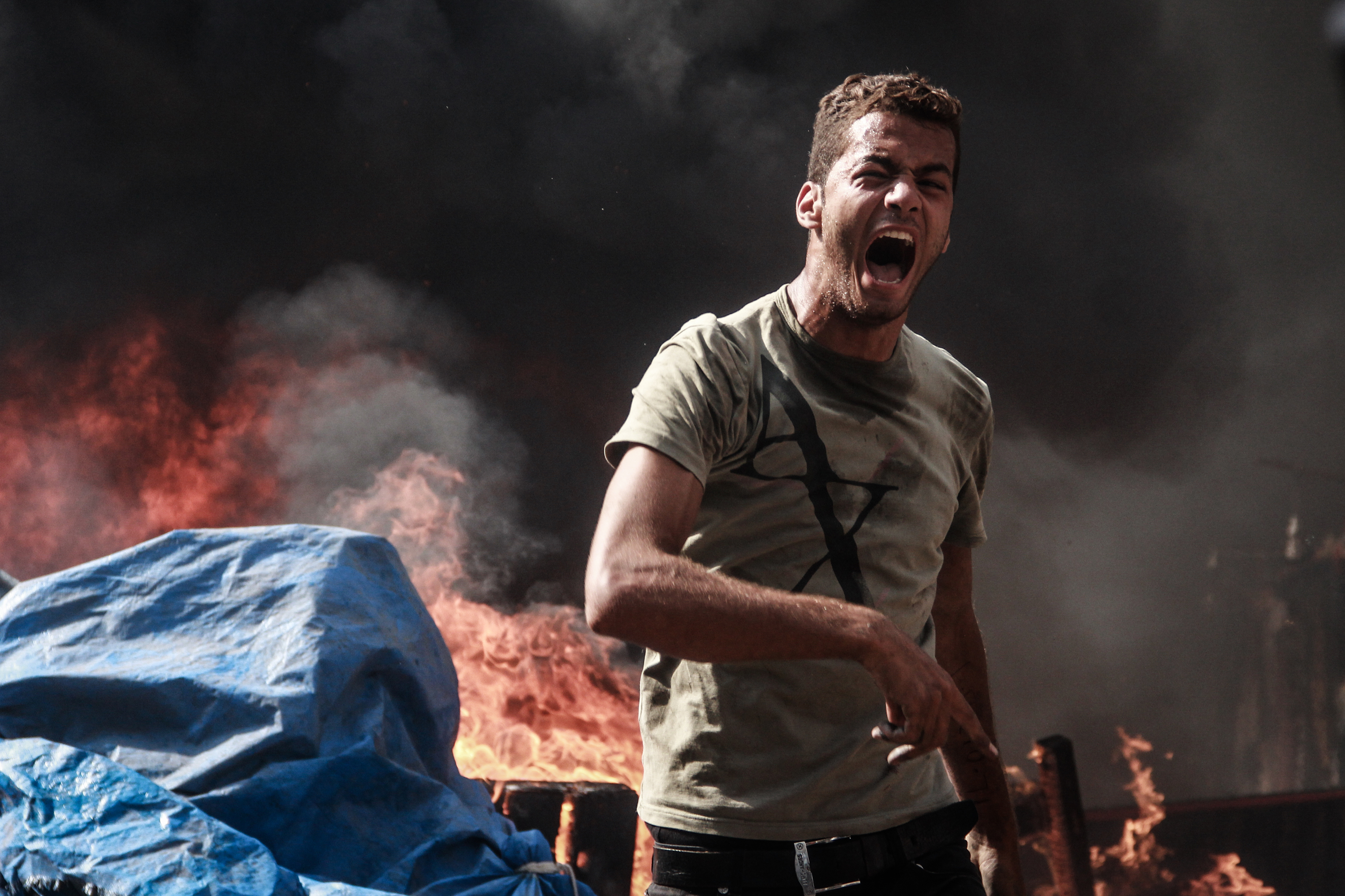 A man yells in the burning ruins of the square.