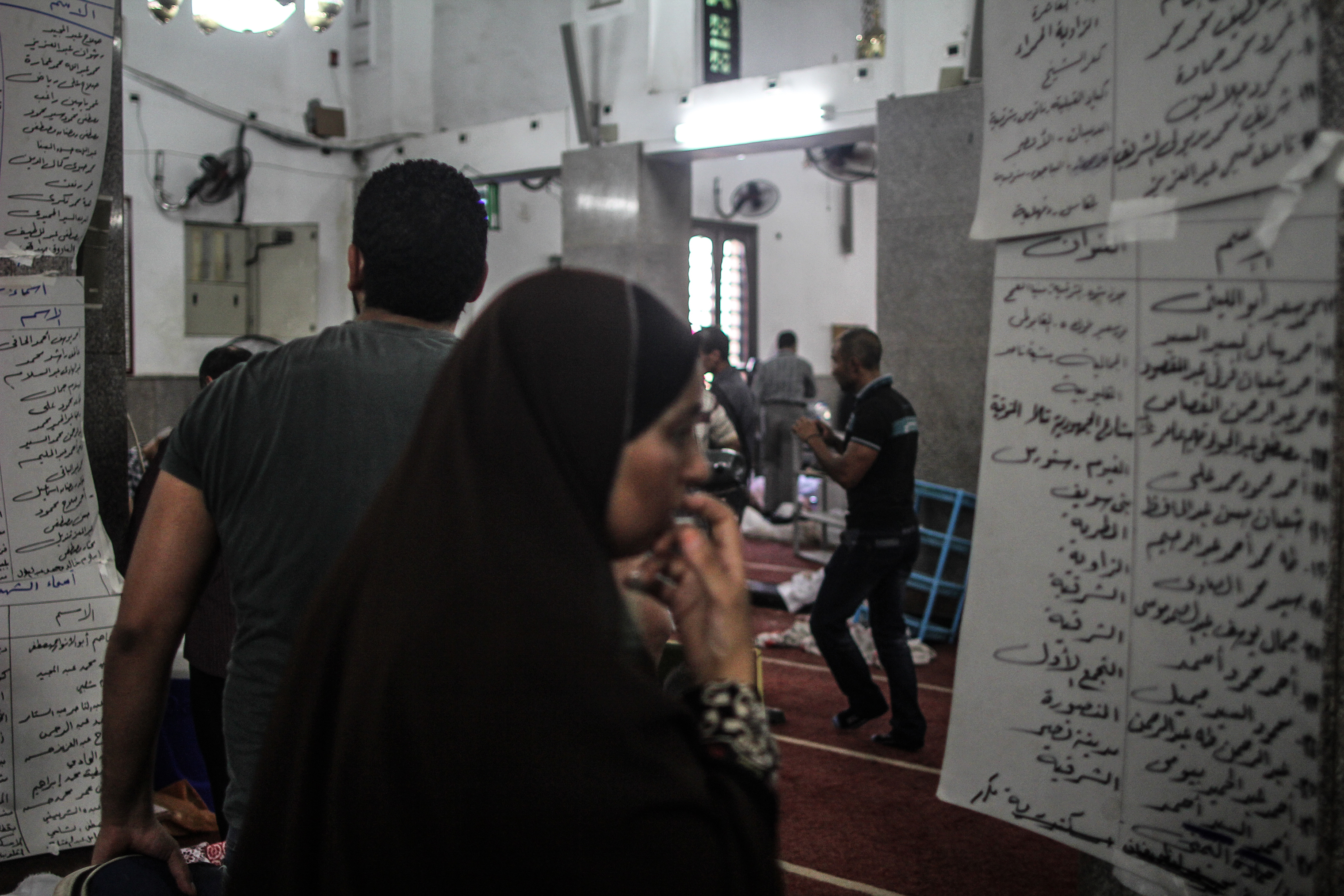 The next day, at a mosque where the bodies were transferred, a distraught mother searches for her son's name on a list showing who had been killed.