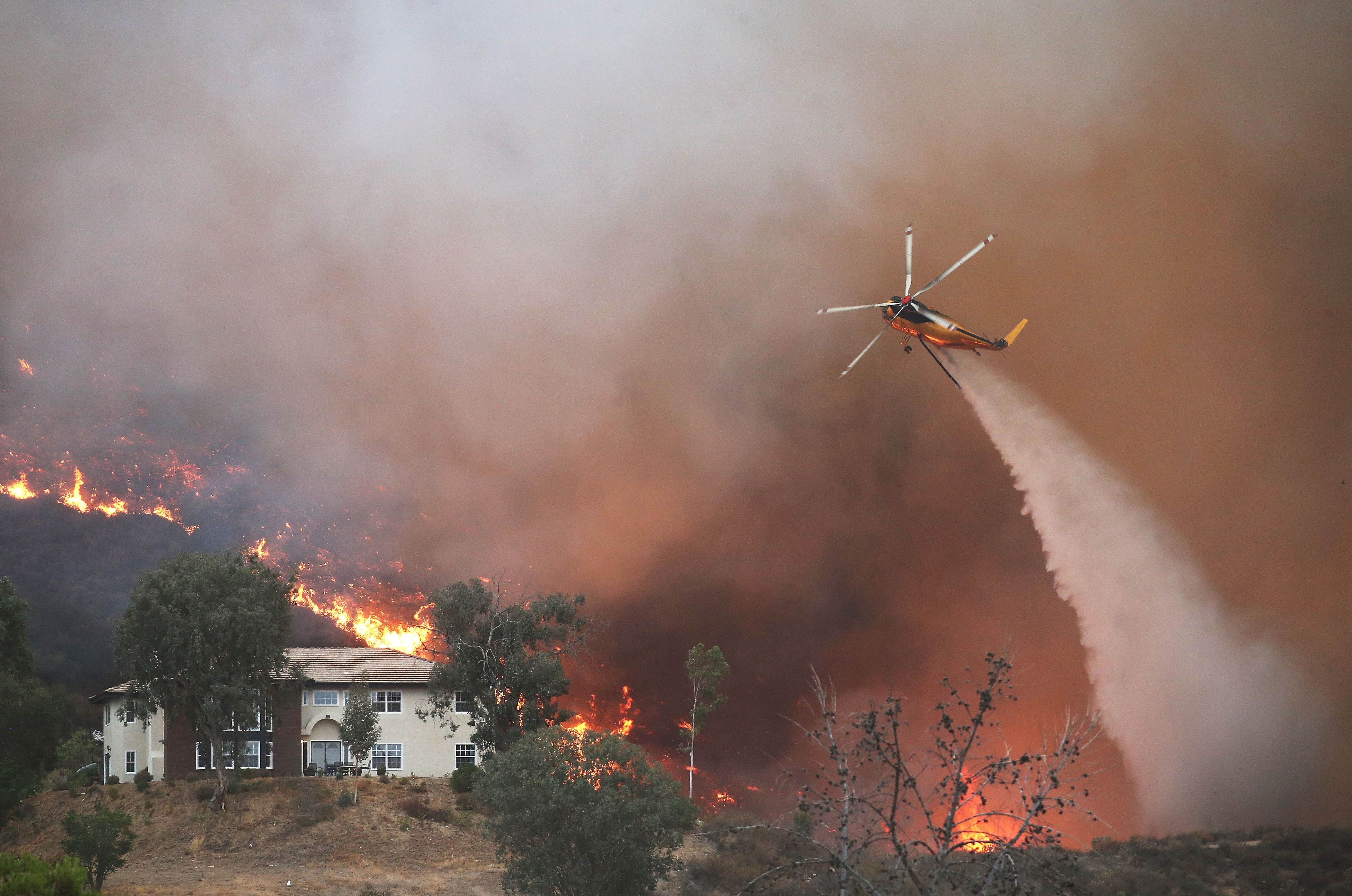 A firefighting helicopter makes a water drop as the Holy Fire burns near homes on August 9, 2018 in Lake Elsinore, California.