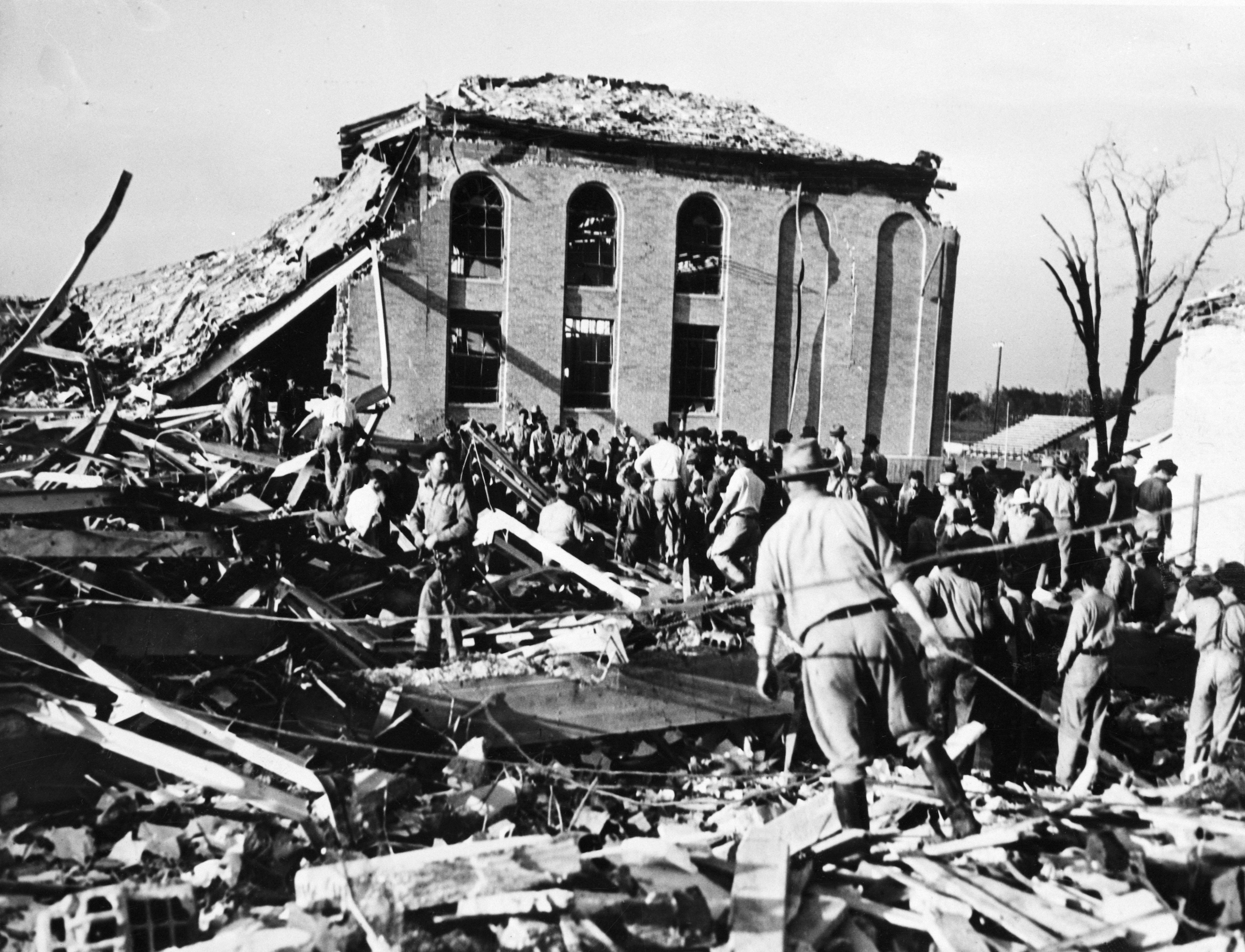 Frantic parents, rescue workers and oil field employees probe a tangled and twisted mass of wreckage after a terrific explosion had leveled all but this corner of the New London High School, near Overton, Tex, in March of 1937.