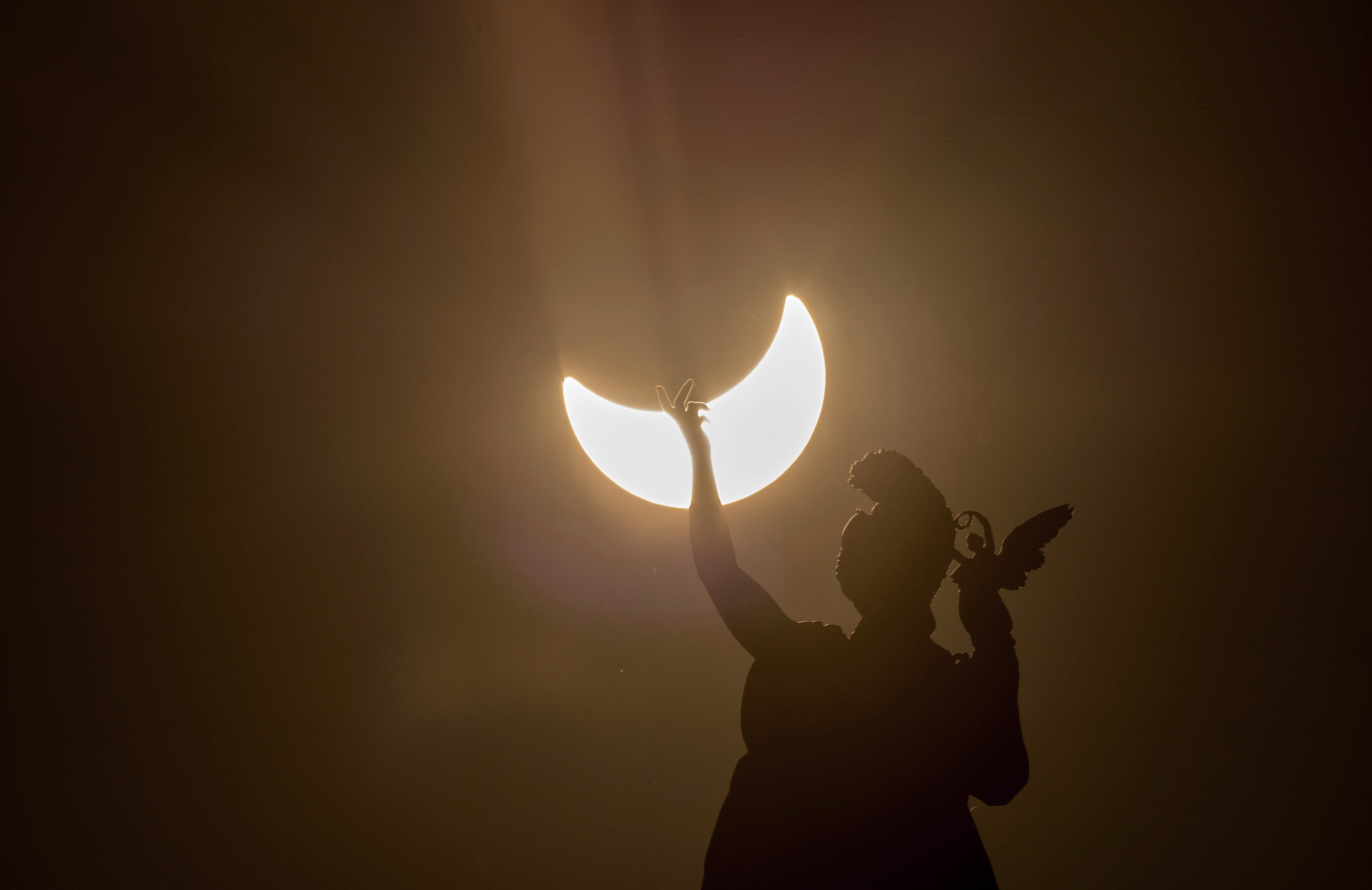 A partial solar eclipse is visible over a statue. (Photo credit should read JOE KLAMAR/AFP/Getty Images)
