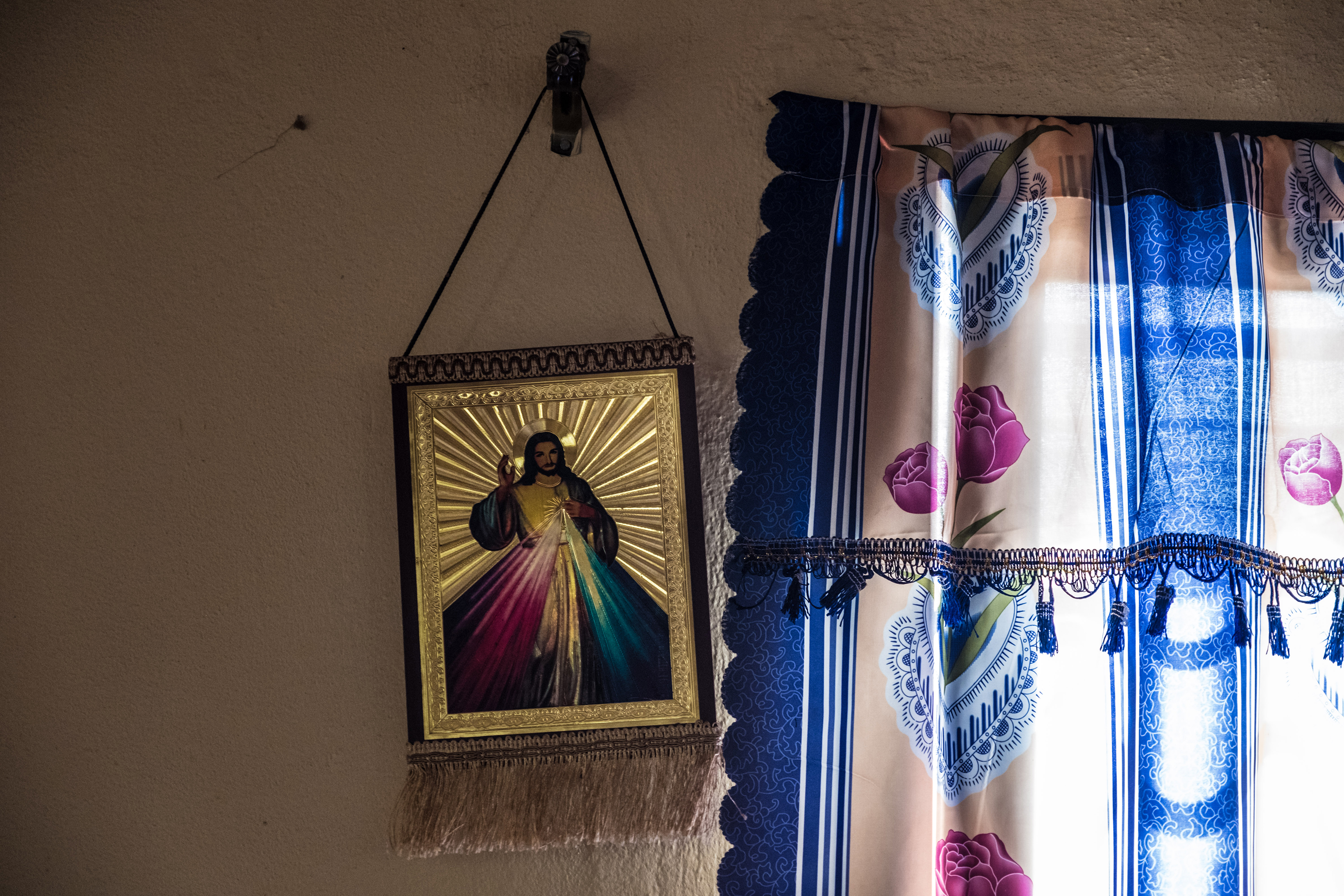 A painting of Jesus hangs on the wall of a building rented by Pastor Emmanuel Momoh, the diamond mining team sponsor.