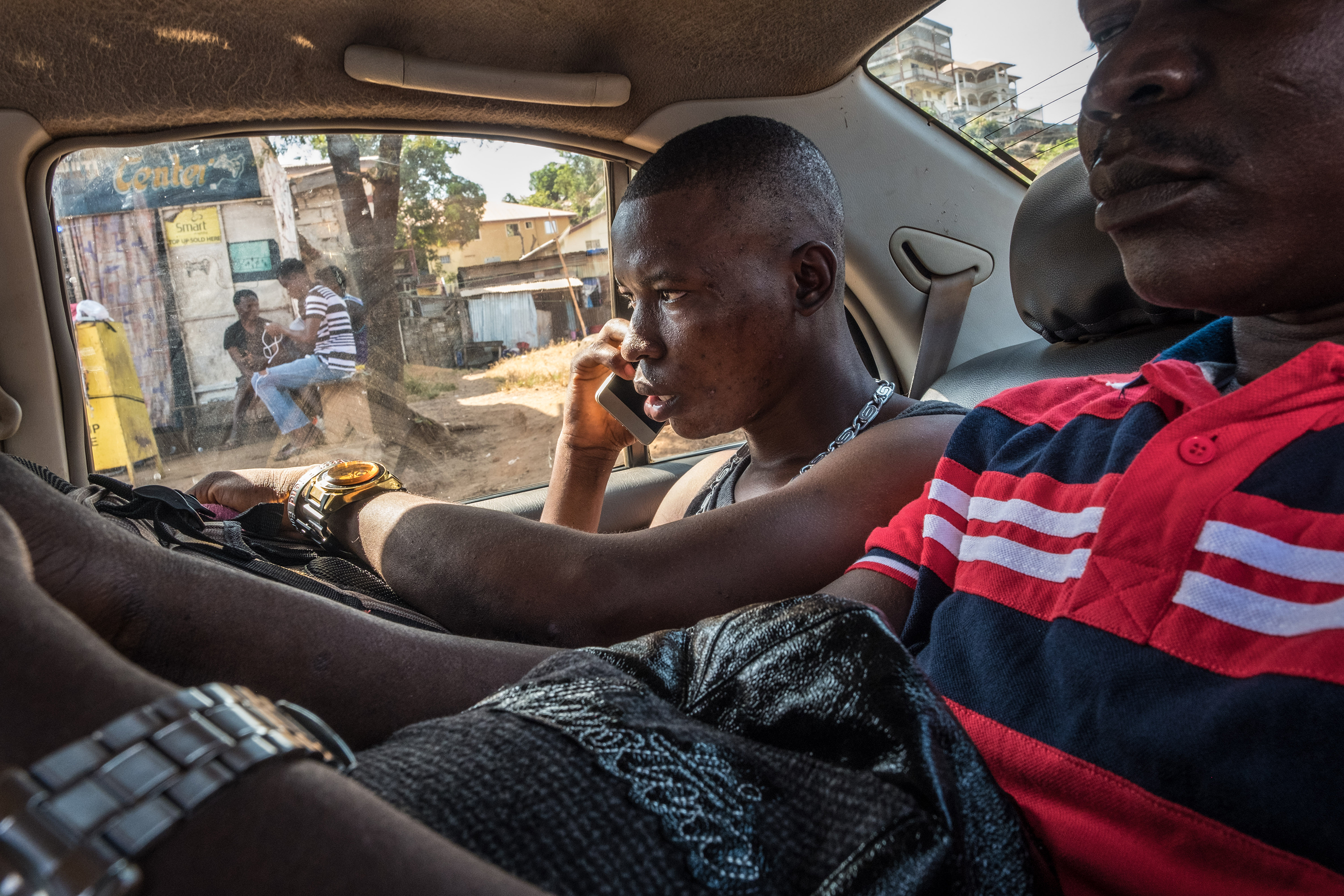 Johnbull, who decided to leave Sierra Leone to pursue an education abroad, travels with his uncle in a taxi to the ferry terminal on the morning of his departure to Ghana.