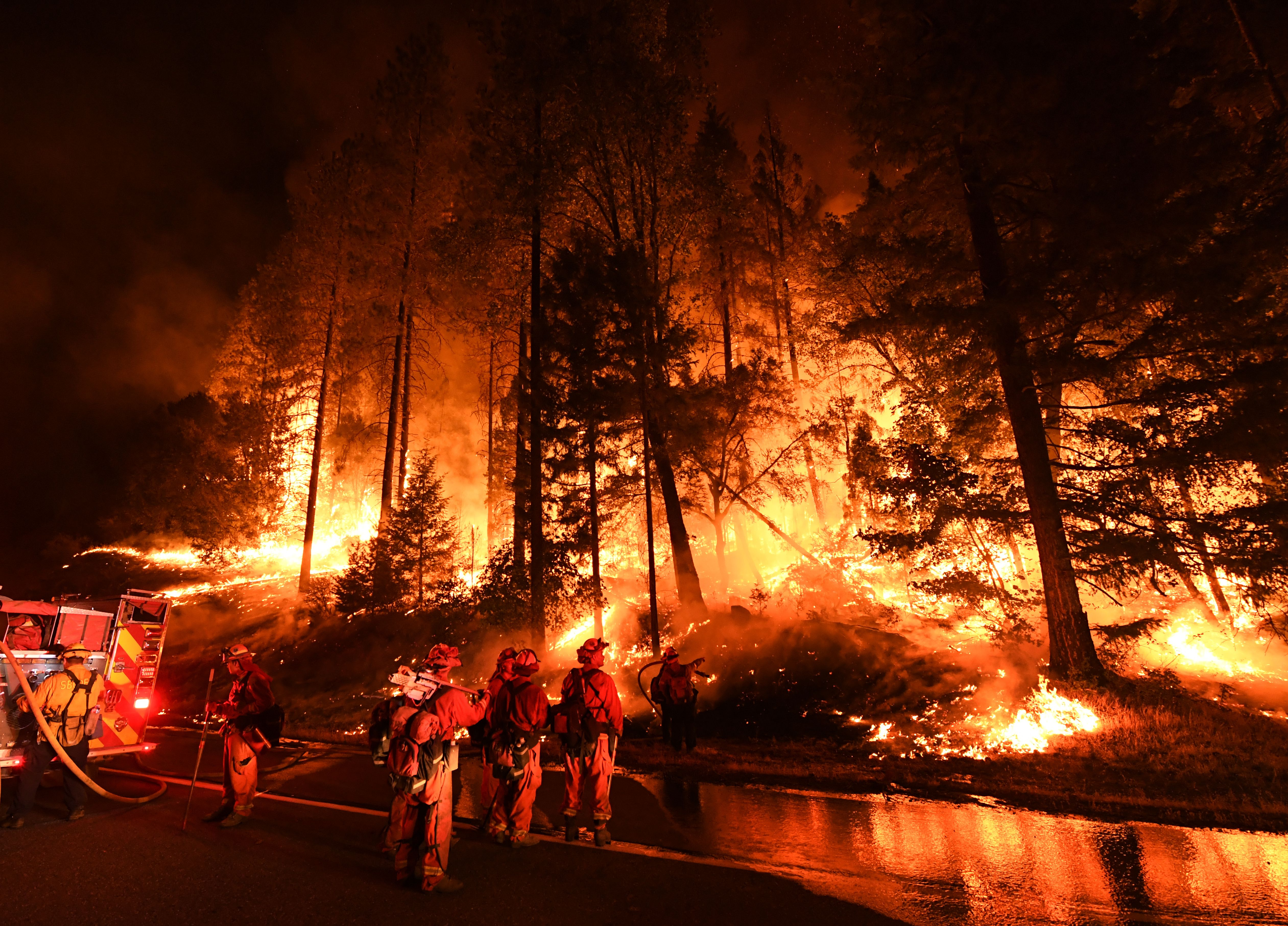 Firefighters try to control a back burn as the Carr fire continues to spread towards the towns of Douglas City and Lewiston near Redding, California on July 31, 2018. Two firefighters were killed fighting the blaze and three people, a 70 year old woman and her two great-grandchildren age four and five, perished when their Redding home was rapidly swallowed up by flames.