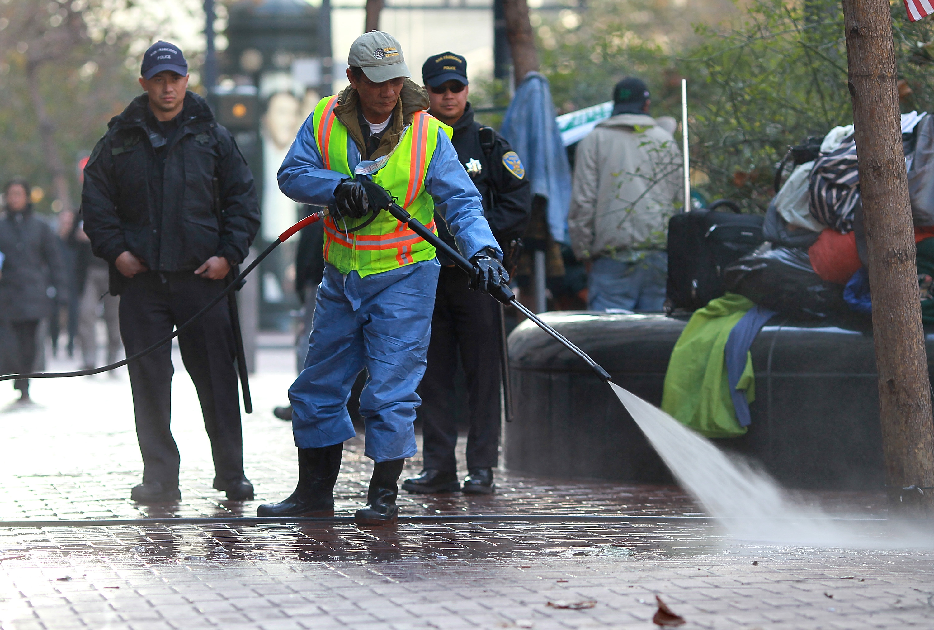 San Francisco police officers look on as a San Francisco Department of Public Works worker steam cleans the street on Dec. 8, 2011 in San Francisco, California.