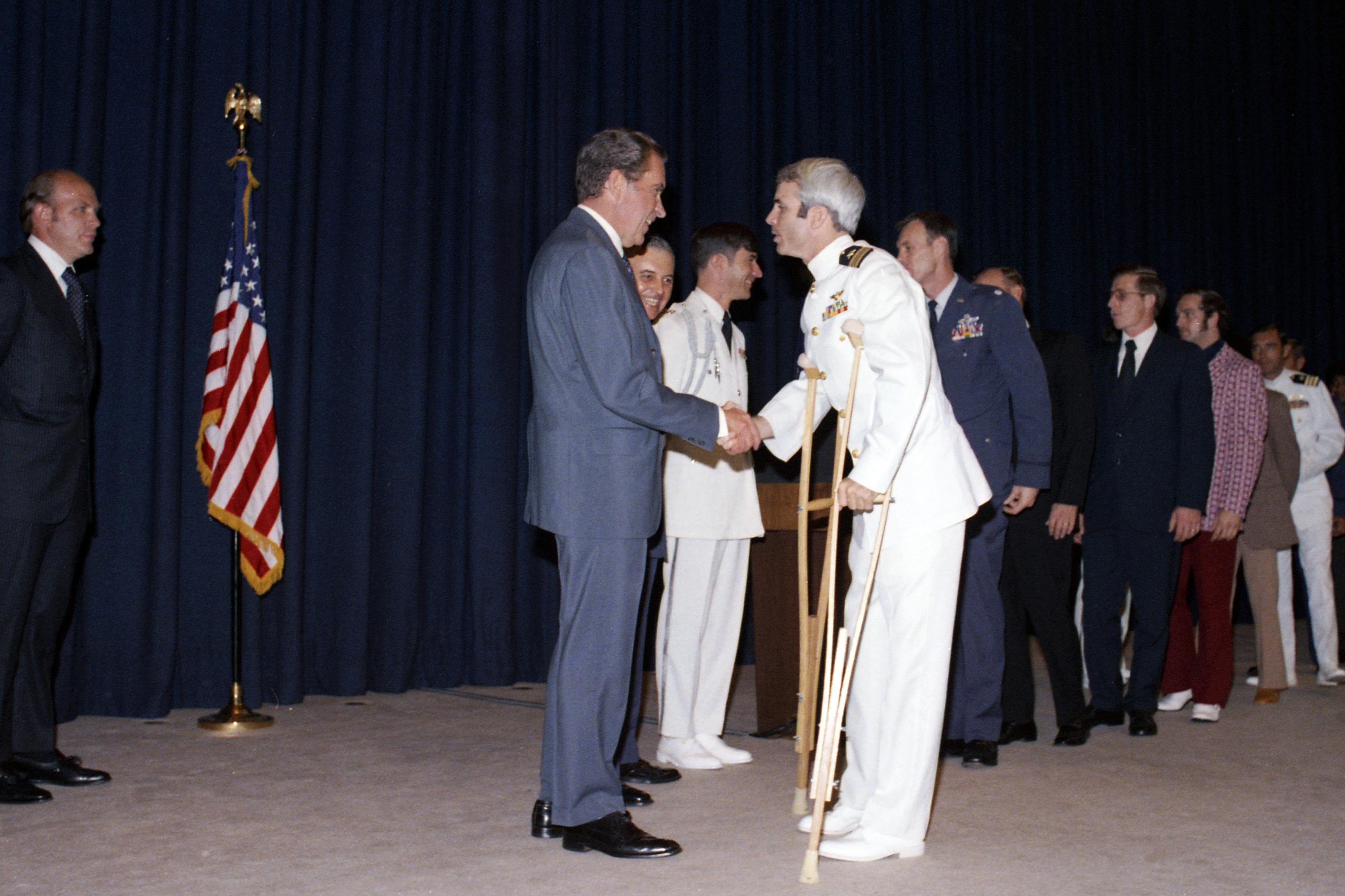 At a pre-dinner reception, US President Richard Nixon (1913 - 1994) greets former North Vietnamese prisoner of war Lieutenant Commander John McCain, in Washington DC, on May 24, 1973.
