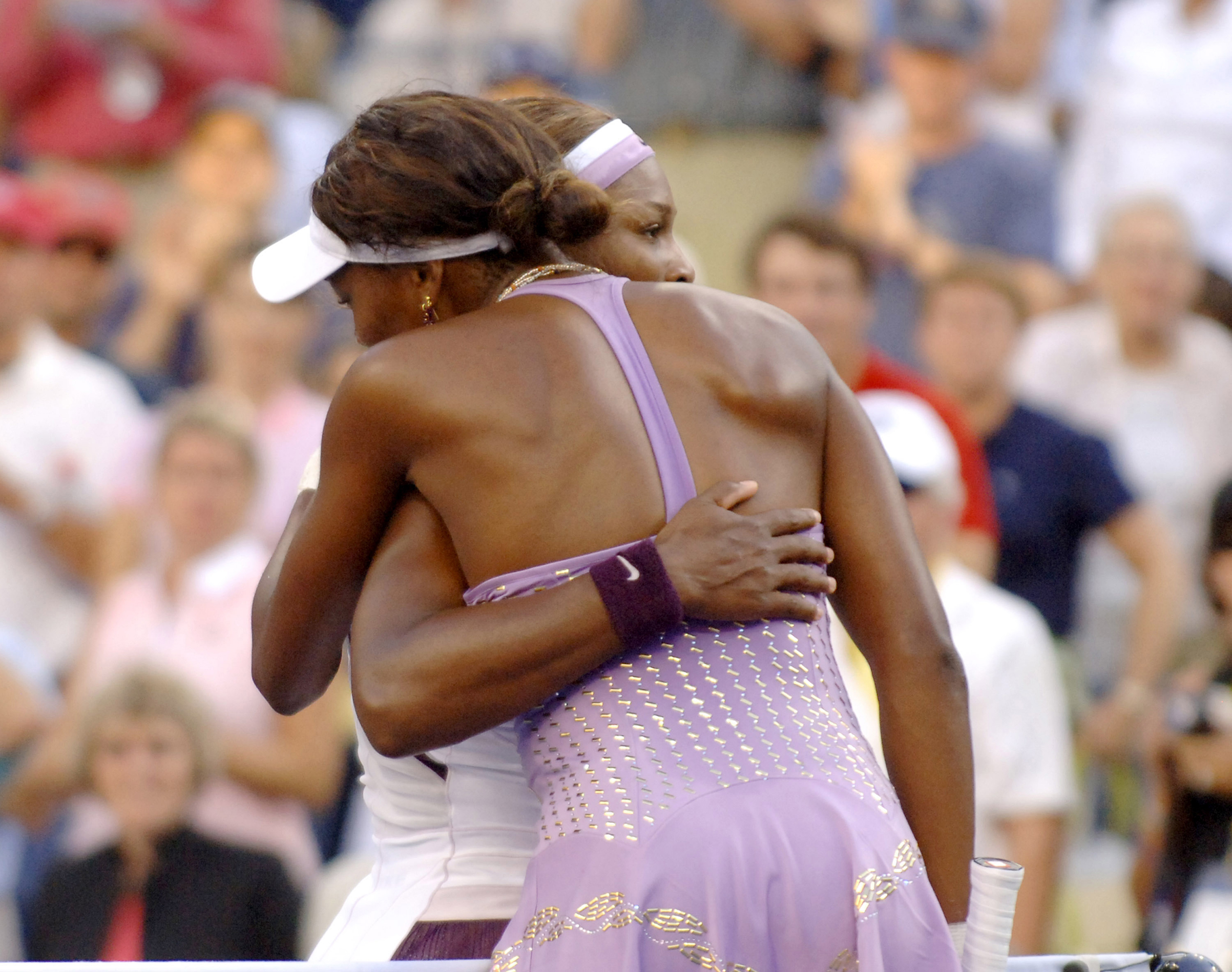 Serena Williams hugs her sister, Venus, after play in a 7-6 6-2 women's quarter final match at the 2005 U. S. Open in Flushing, New York.