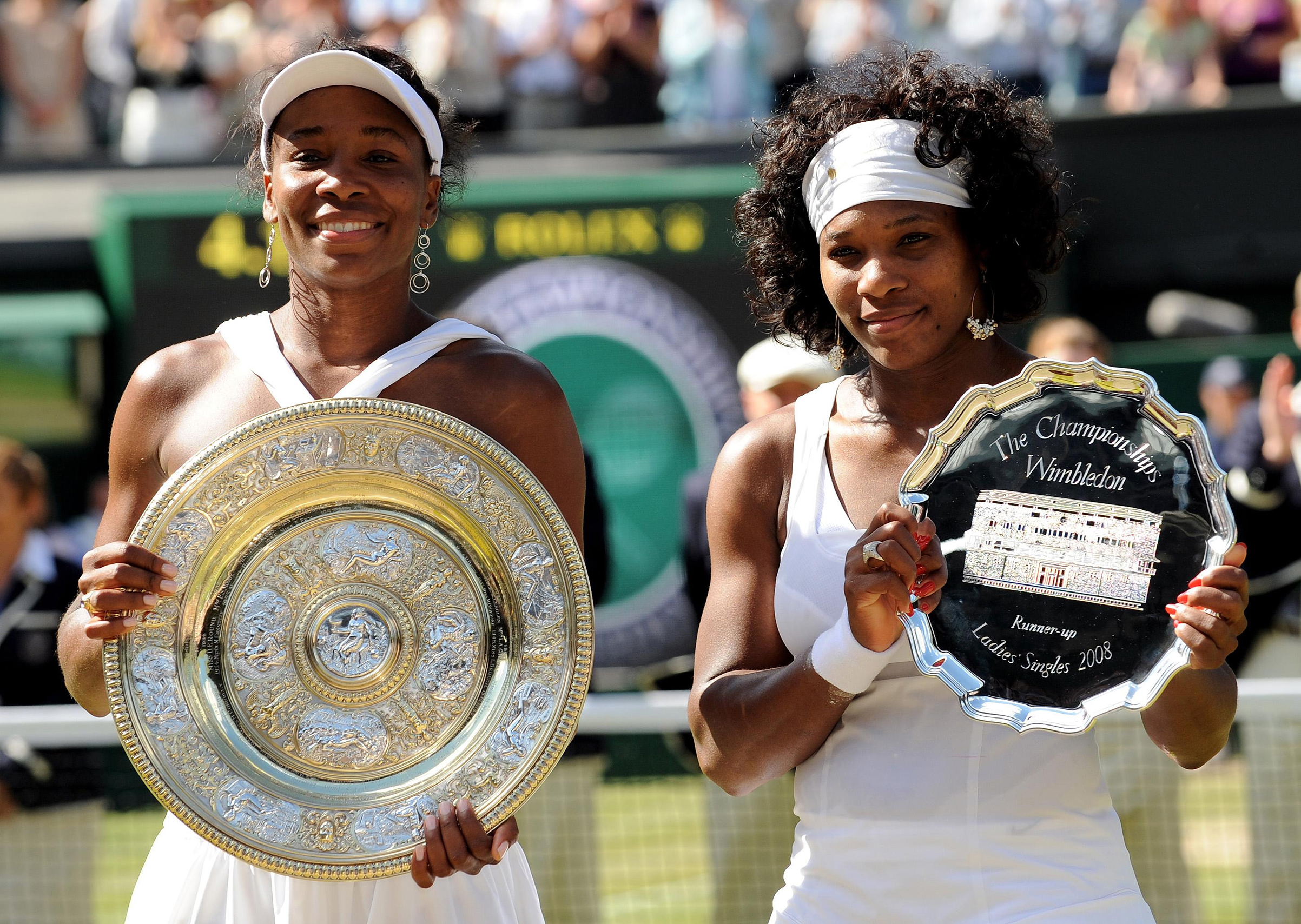 USA's Venus Williams and USA's Serena Williams with their trophies following their Women's Final match during the Wimbledon Championships 2008 at the All England Tennis Club in Wimbledon.