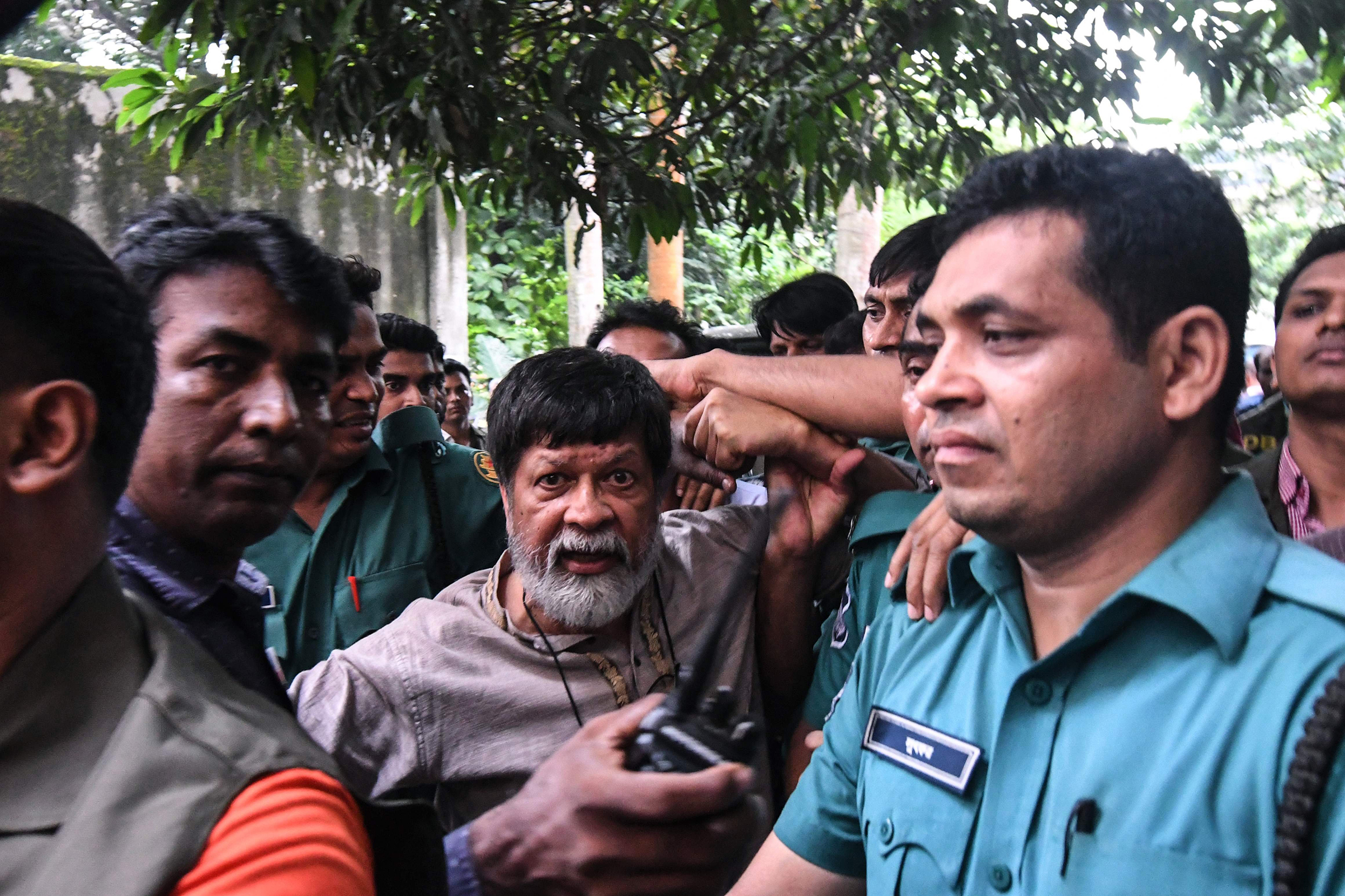 Activists and photographer Shahidul Alam arrives surrounded by policemen for a court appearance in Dhaka on Aug. 6, 2018.