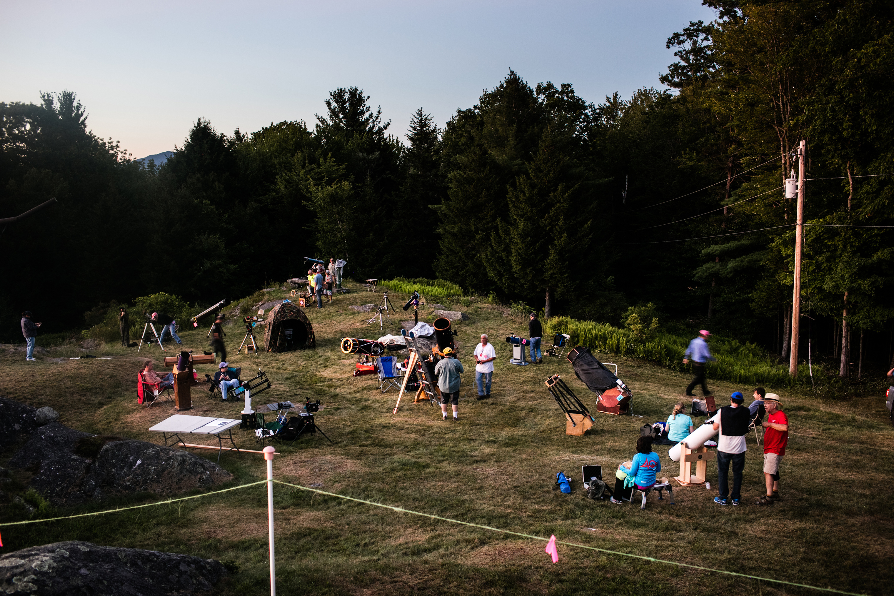 As the sun starts to set, people set up their telescopes, many of which are home-made, on Breezy Hill in Springfield, Vermont.