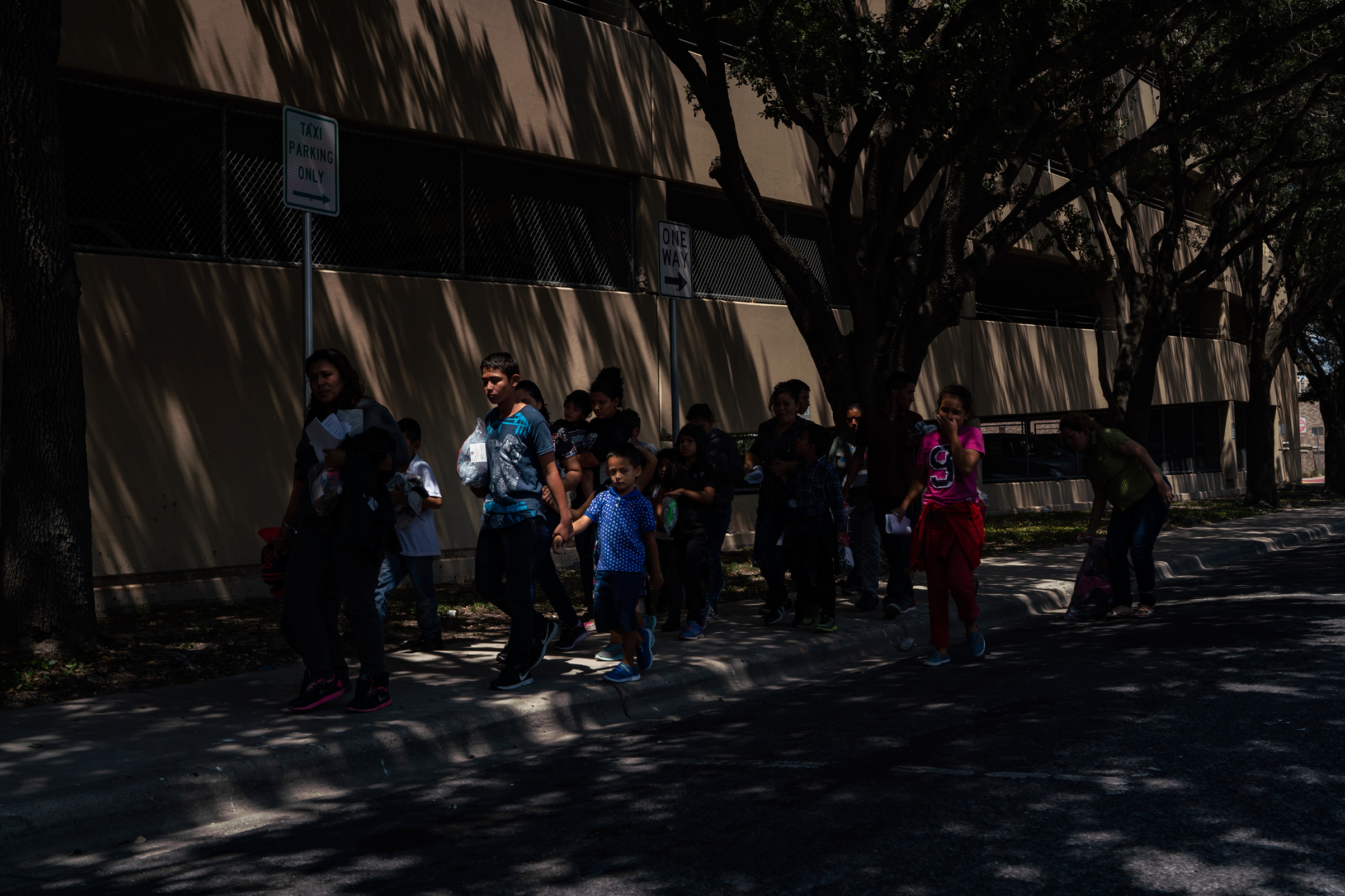 Central American asylum seekers walk to the nearby Catholic Charities Humanitarian Respite Center after being dropped off at the McAllen bus station on Aug. 2, 2018.
